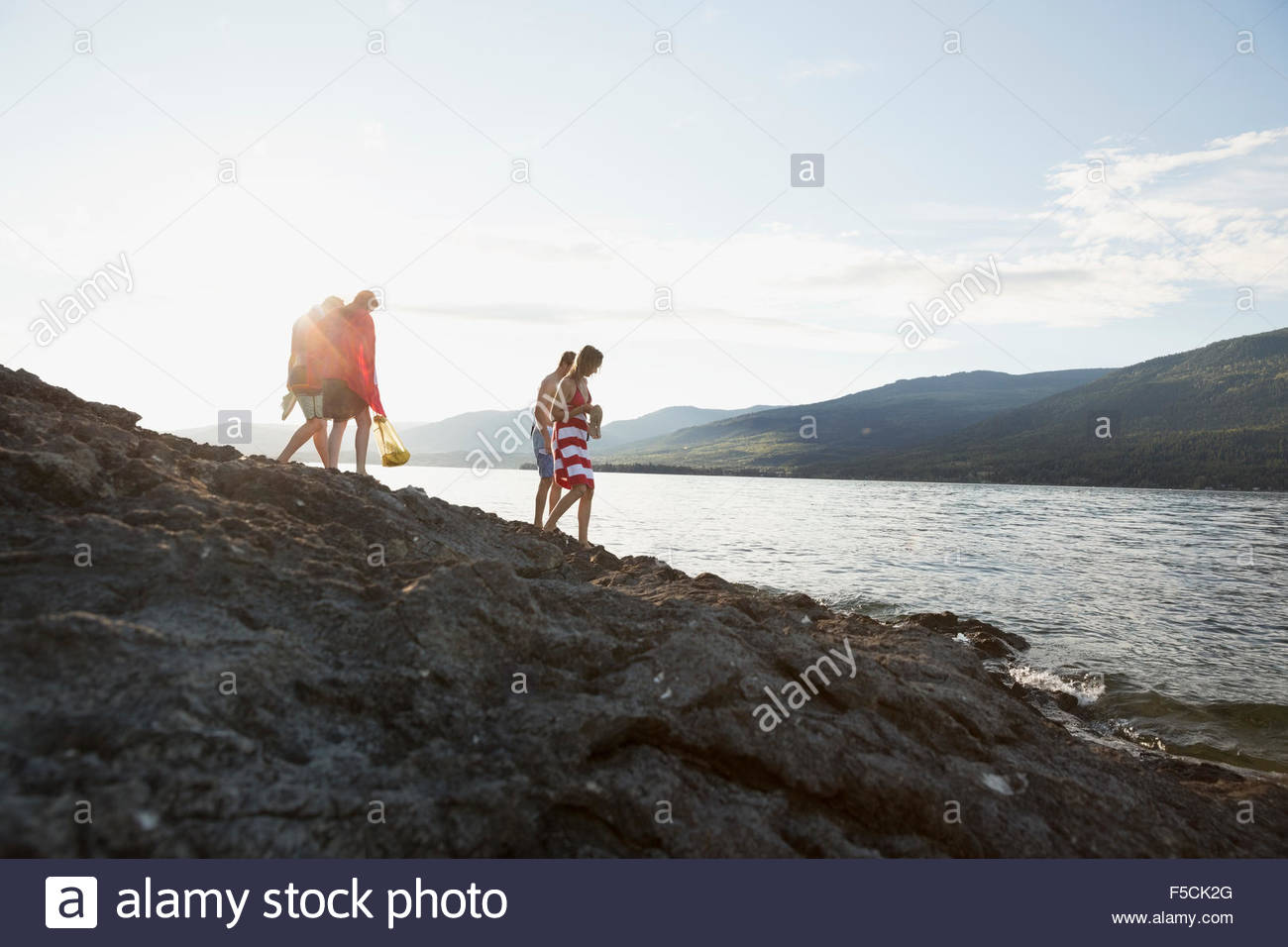 Junge Freunde, die zu Fuß auf den Felsen am sonnigen See Stockfoto
