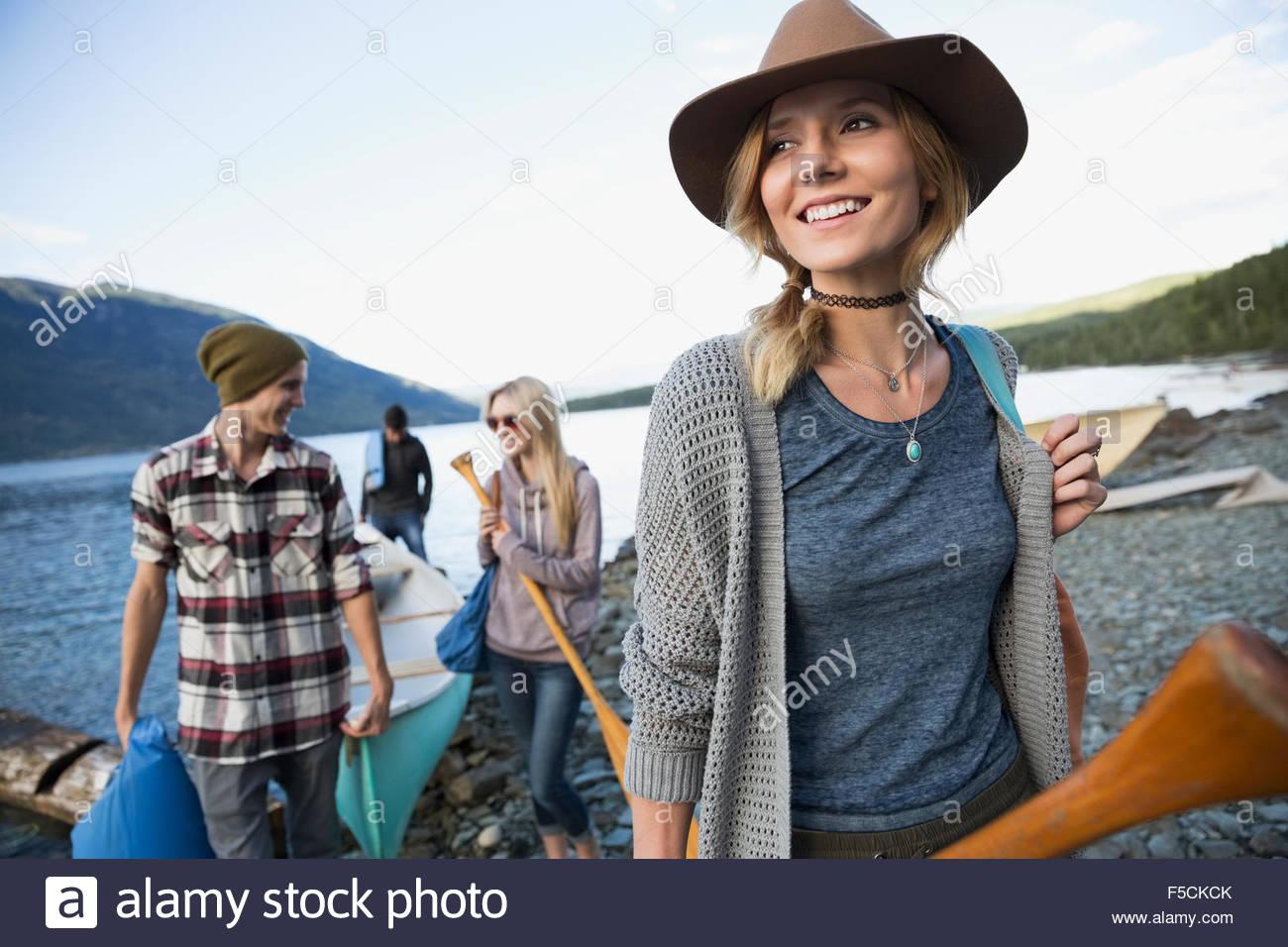 Lächelnde junge Freunde mit Kanu am Seeufer Stockfoto
