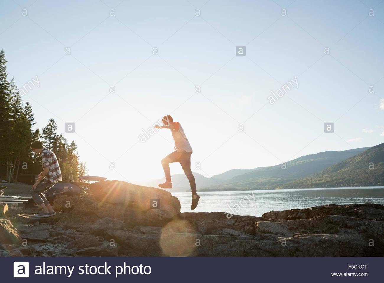 Junge Männer springen über Felsen am sonnigen Seeufer Stockbild