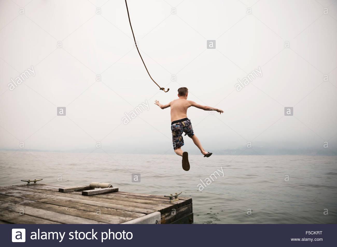 Junge springt mitten in der Luft aus dem Dock in See Stockbild