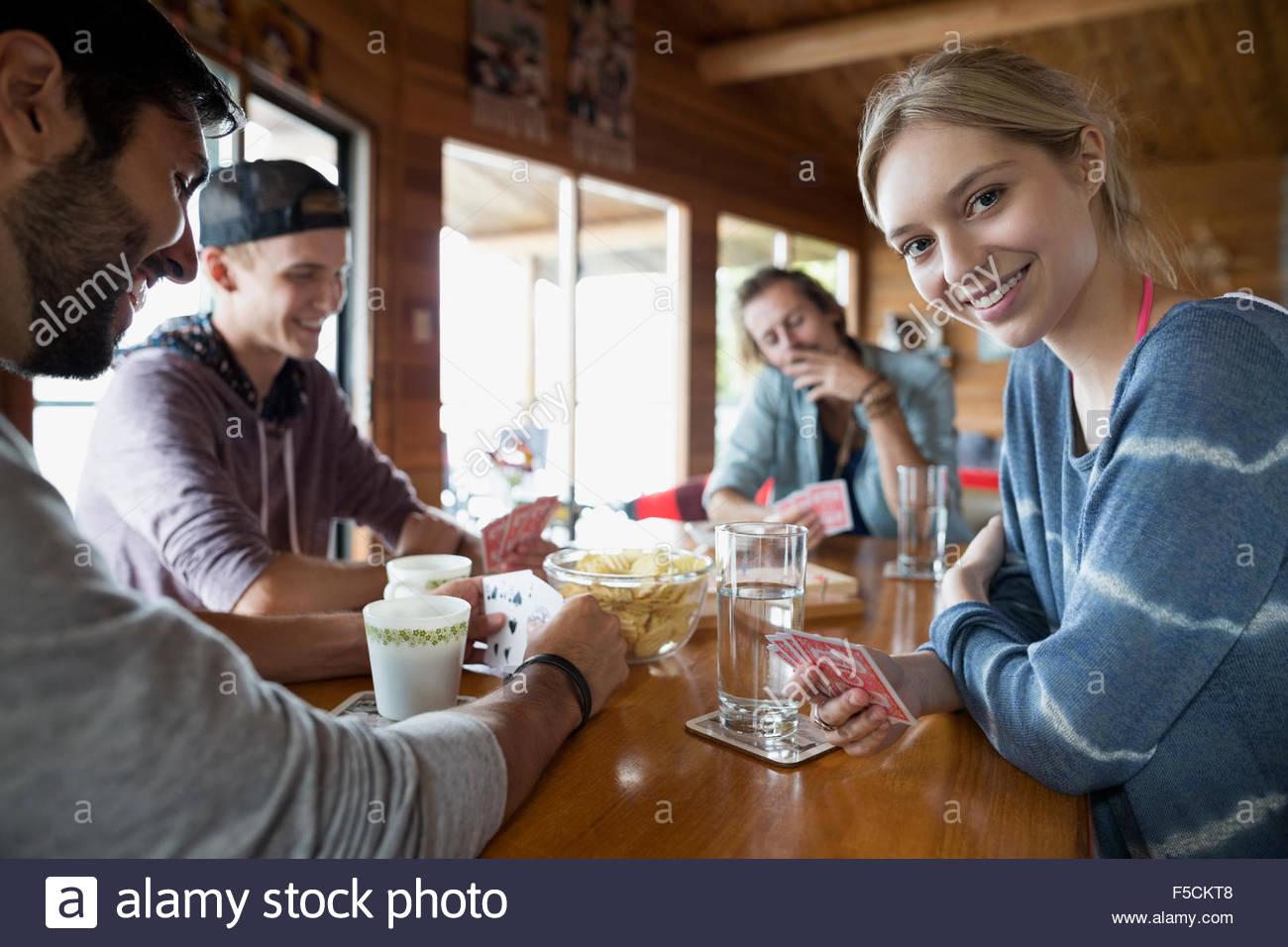 Porträt, lächelnde junge Frau beim Kartenspiel mit Freunden Stockbild