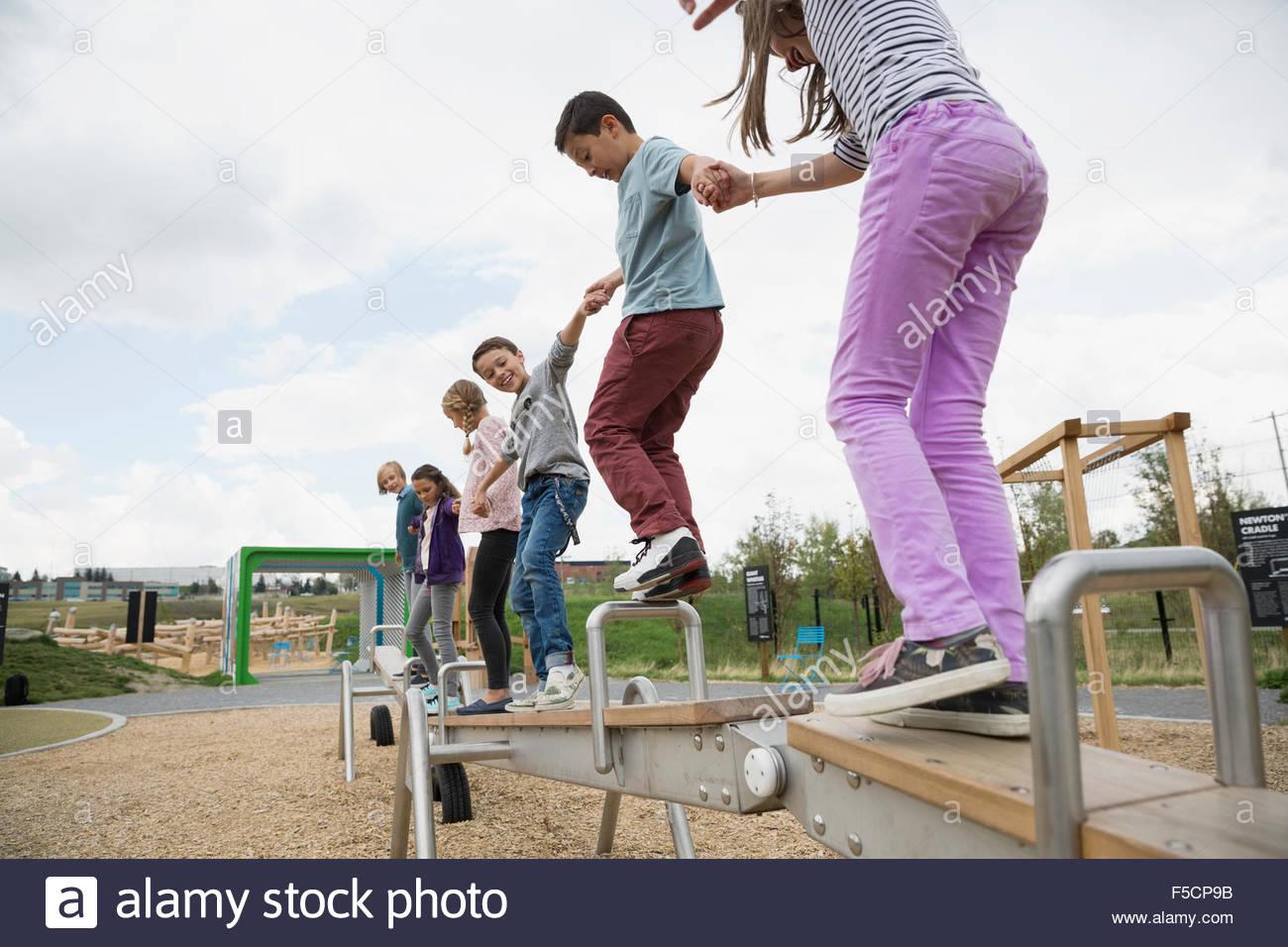 Kinder balancieren auf langen Wippe auf Spielplatz Stockbild