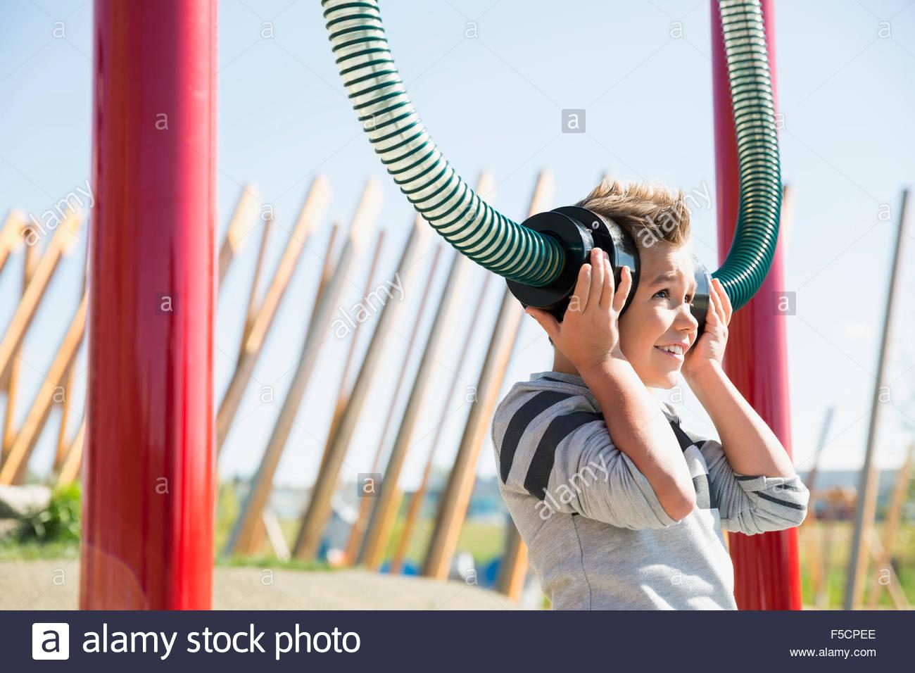 Jungen spielen hören Rohre im sonnigen Spielplatz Stockbild