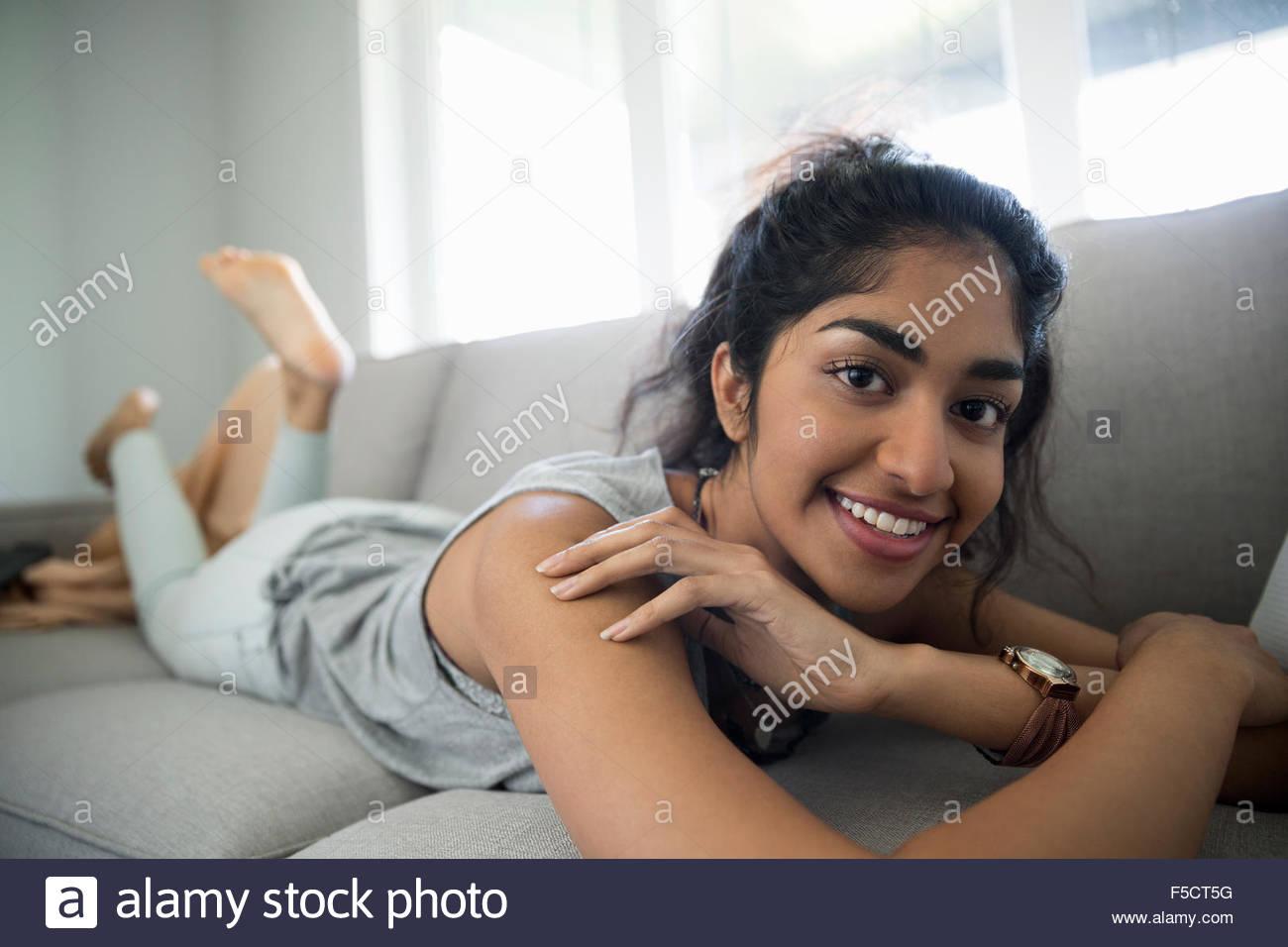 Porträt lächelnde junge Frau entspannend auf sofa Stockbild