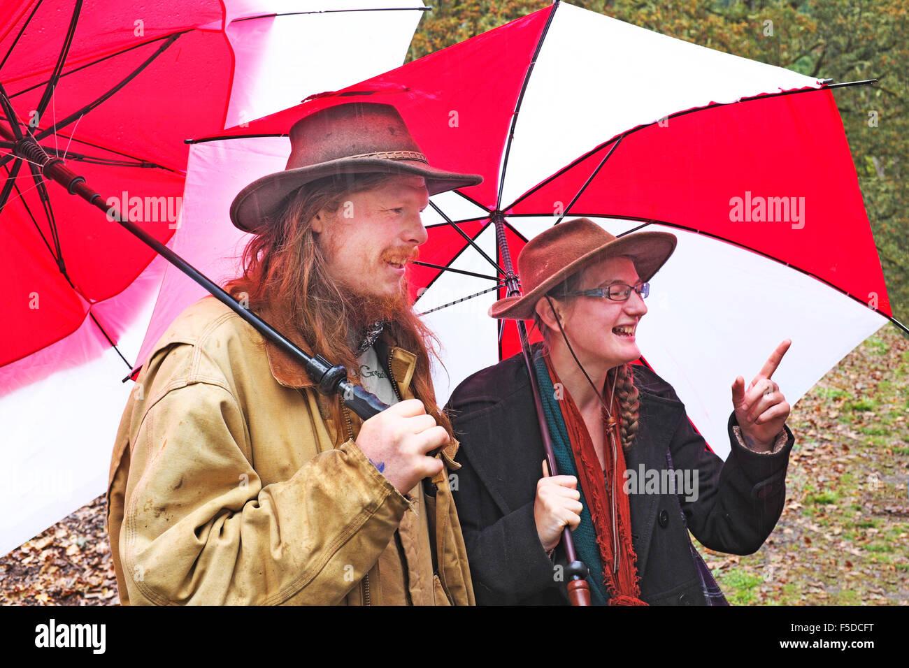Zwei Personen halten rote Sonnenschirme in einem Regen Sturm in Eugene, Oregon Stockbild
