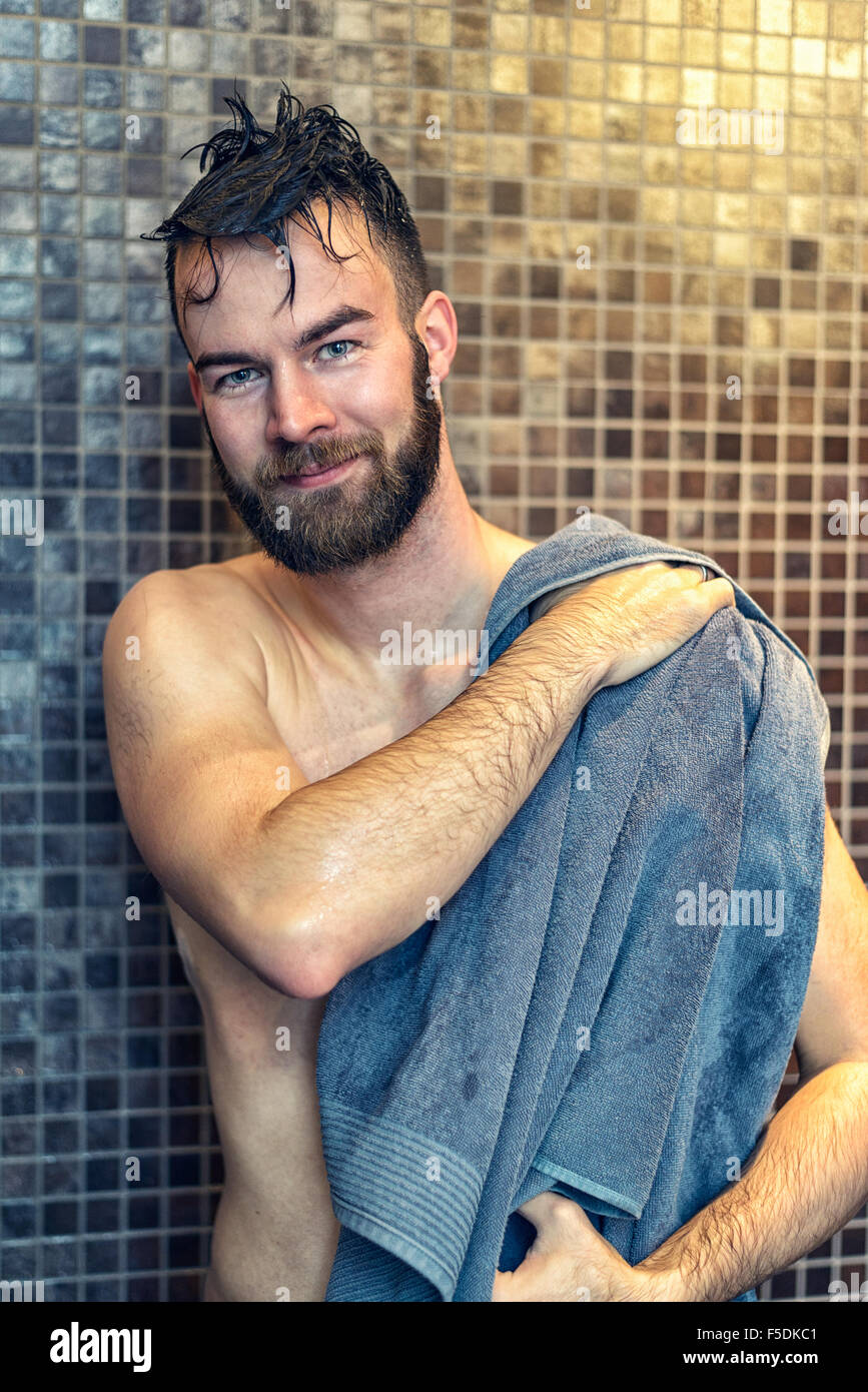 Gutaussehender bärtiger junger Mann sich mit einem Handtuch trocknen, nach dem Genuss einer Dusche im Badezimmer, Stockbild