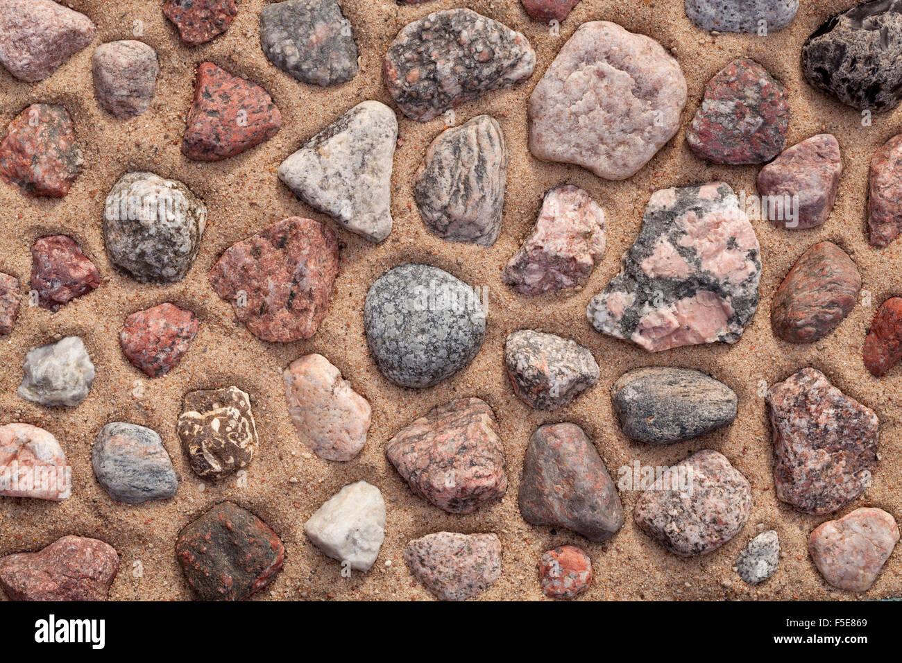 bunten Steinen auf Sand als Hintergrund angeordnet Stockbild