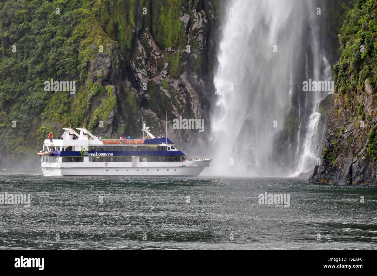 Tourenboot in der Nähe von Stirling Wasserfall, Milford sound, Fiordland National Park, Neuseeland Stockbild