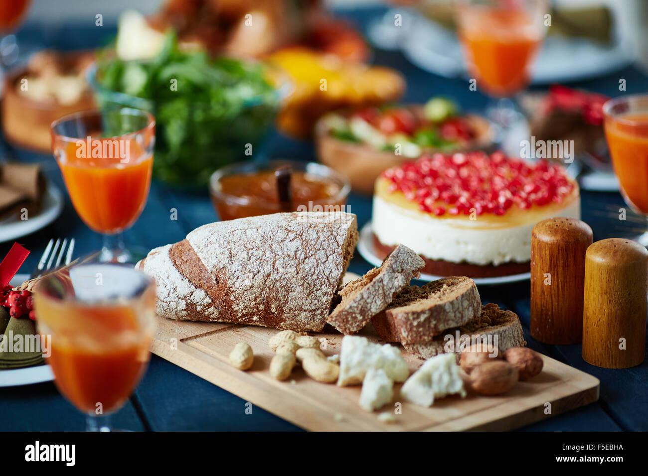 Scheiben von Roggenbrot und andere Lebensmittel auf festlich gedeckten Tisch Stockbild