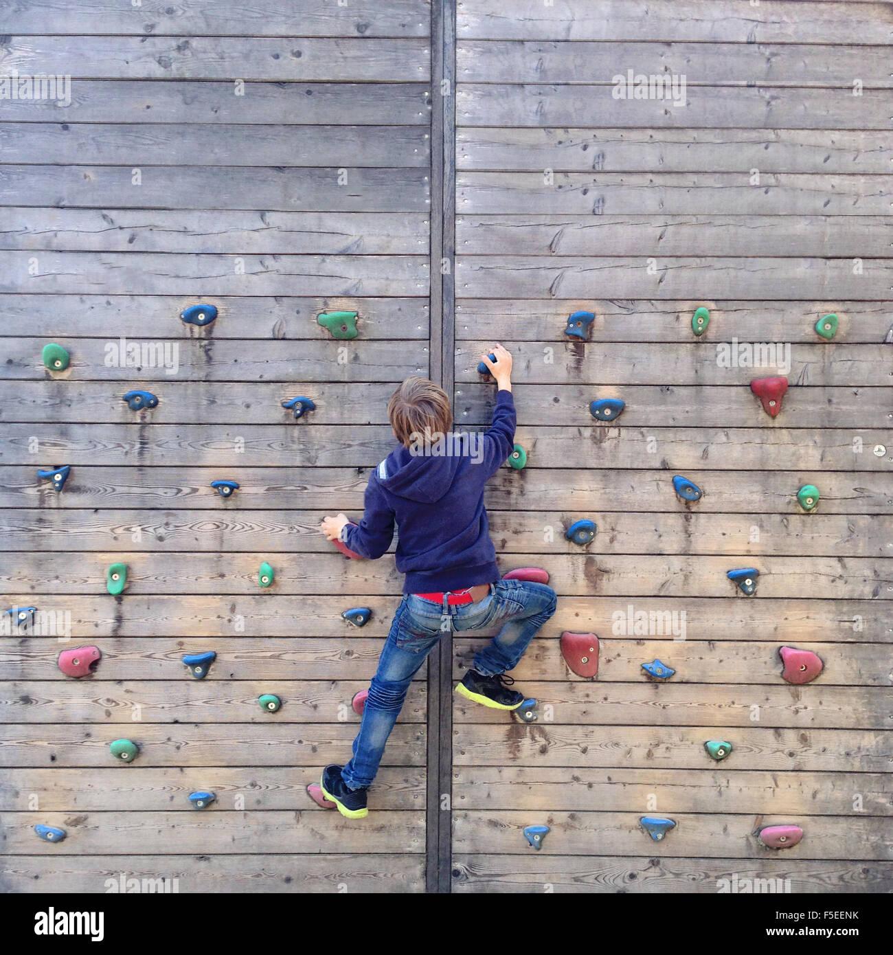 Junge, Klettern an der Kletterwand Stockbild