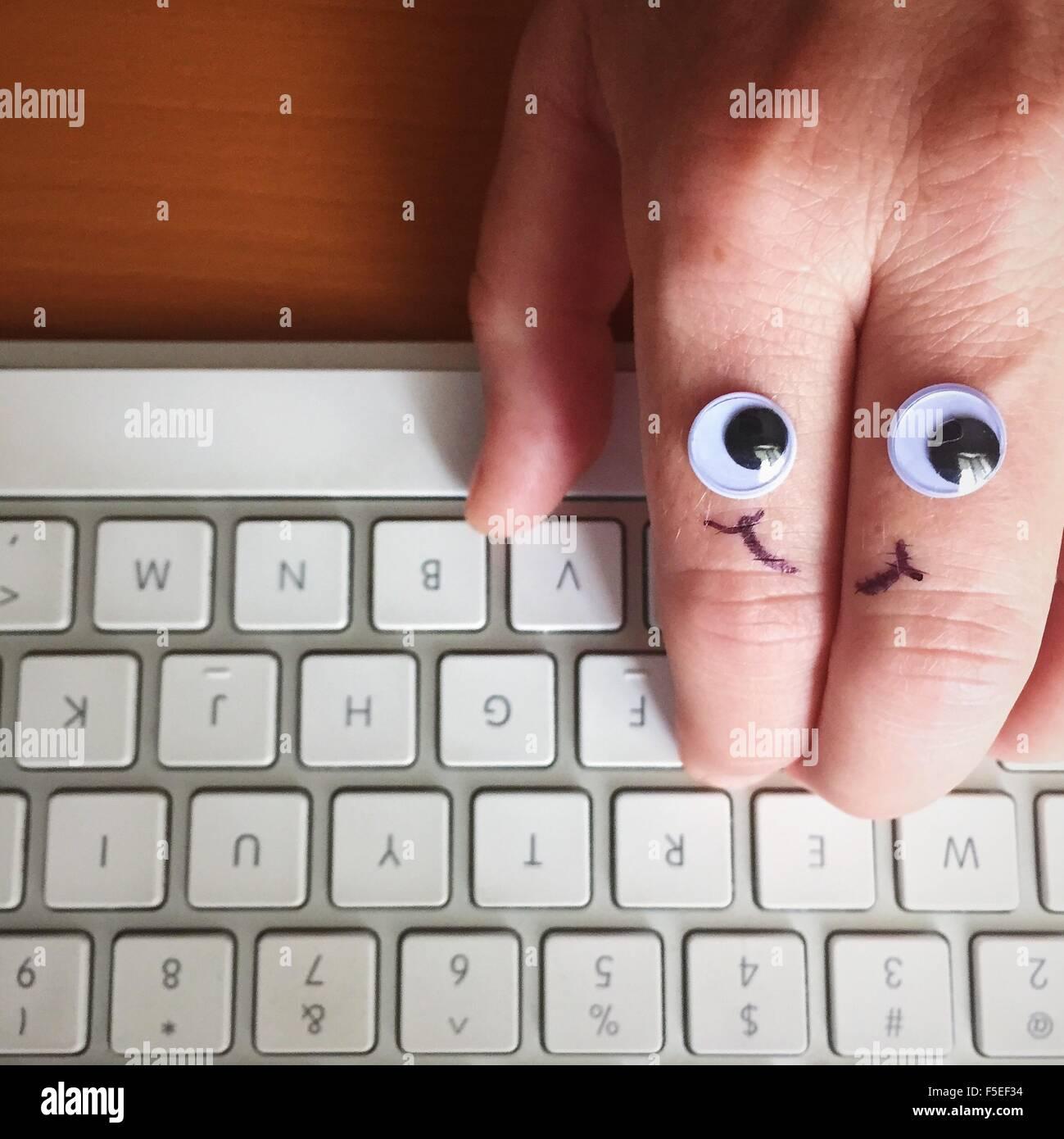 Google Augen und Smiley-Gesicht gezeichnet auf einer Hand Tippen auf Tastatur Stockbild