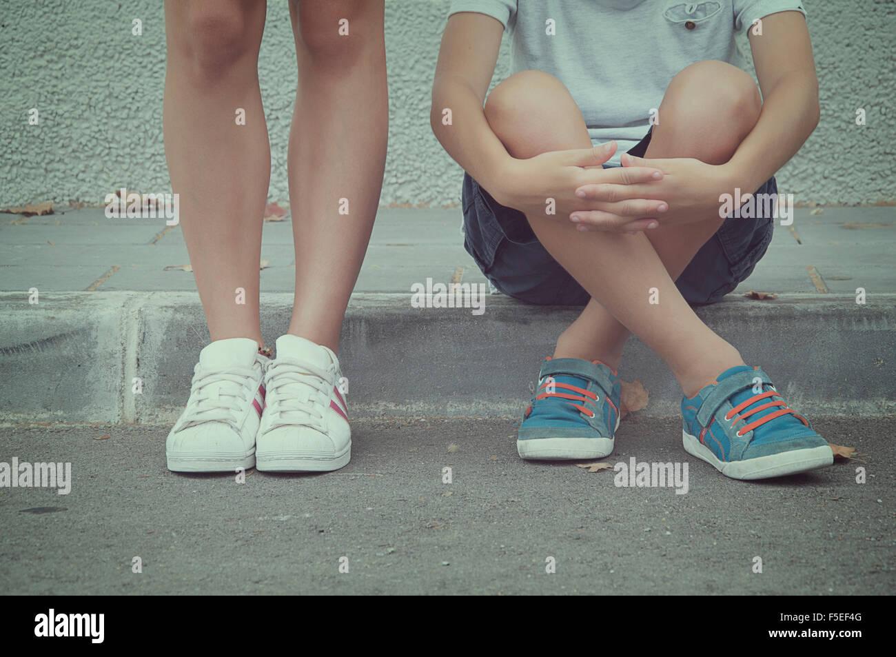 Nahaufnahme der beiden Teenager sitzen und stehen auf der Straße Stockbild