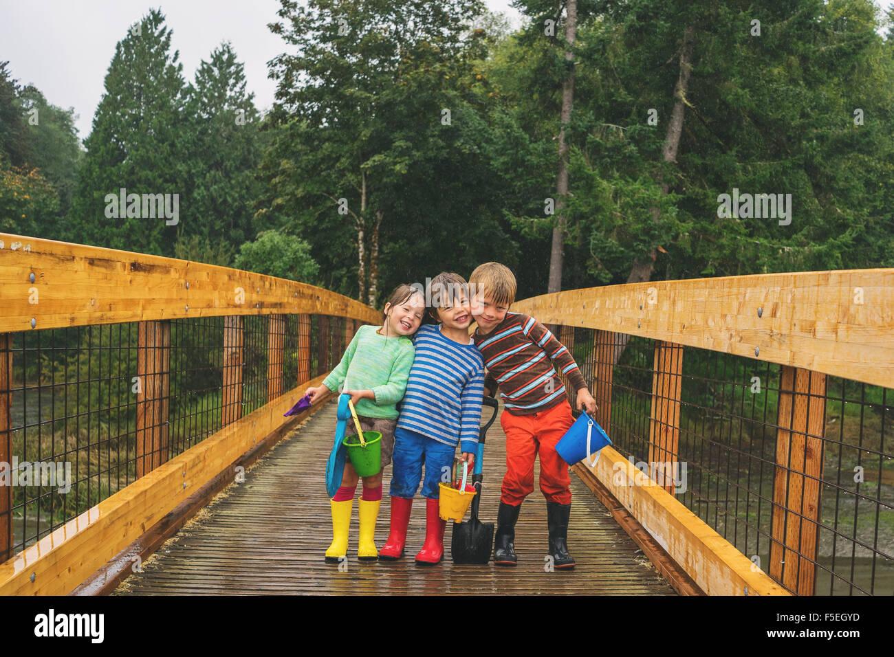 Zwei Jungs und ein Mädchen auf einer Holzbrücke im Regen stehen Stockbild