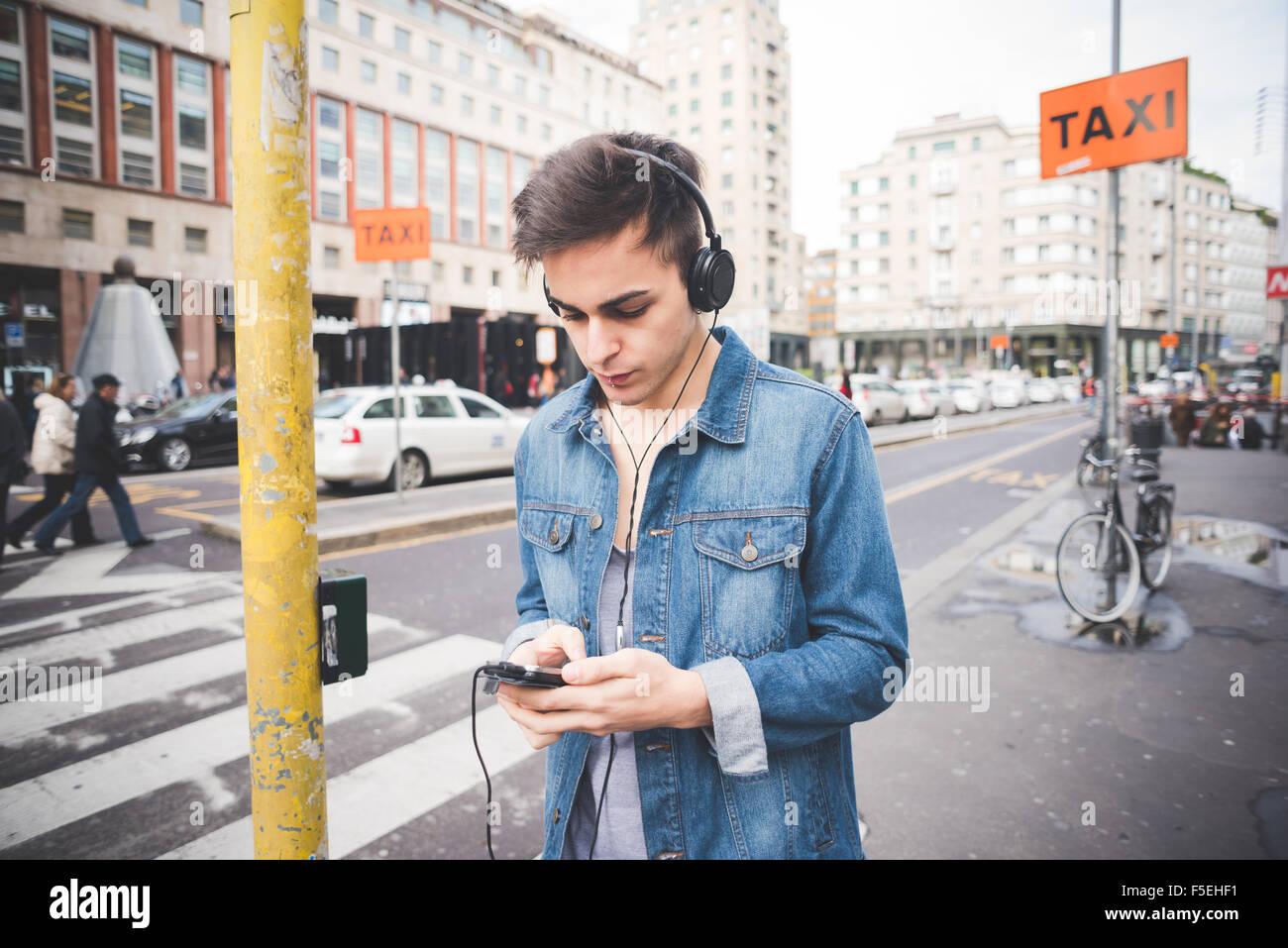 Halbe Länge des jungen schönen dunklen Alternativmodell Mann in der Stadt Musikhören mit Kopfhörer Stockbild