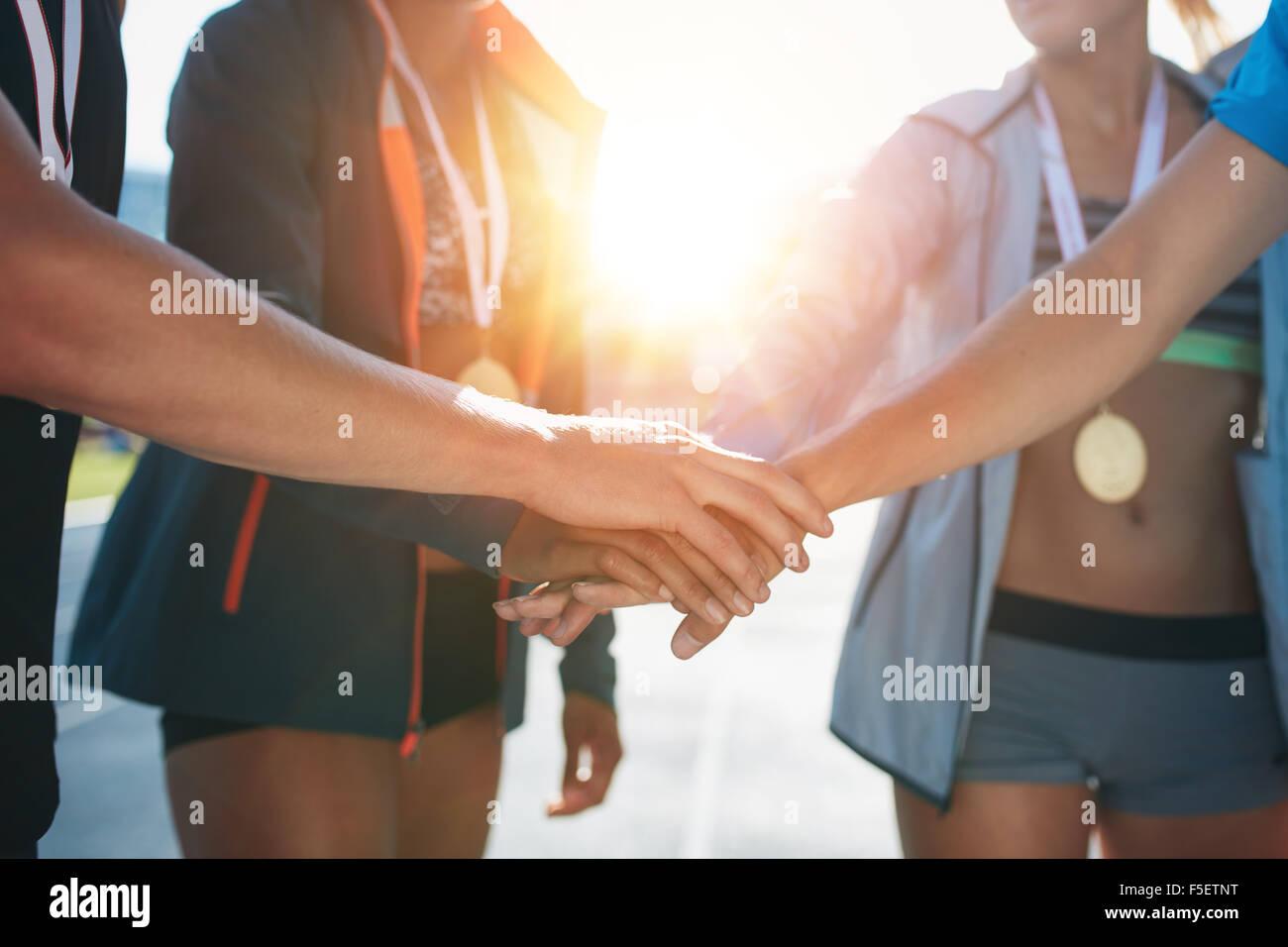 Sportler mit Händen im Huddle zusammen. Team mit Händen gemeinsam Erfolge feiern, nachdem er Leichtathletik Stockbild