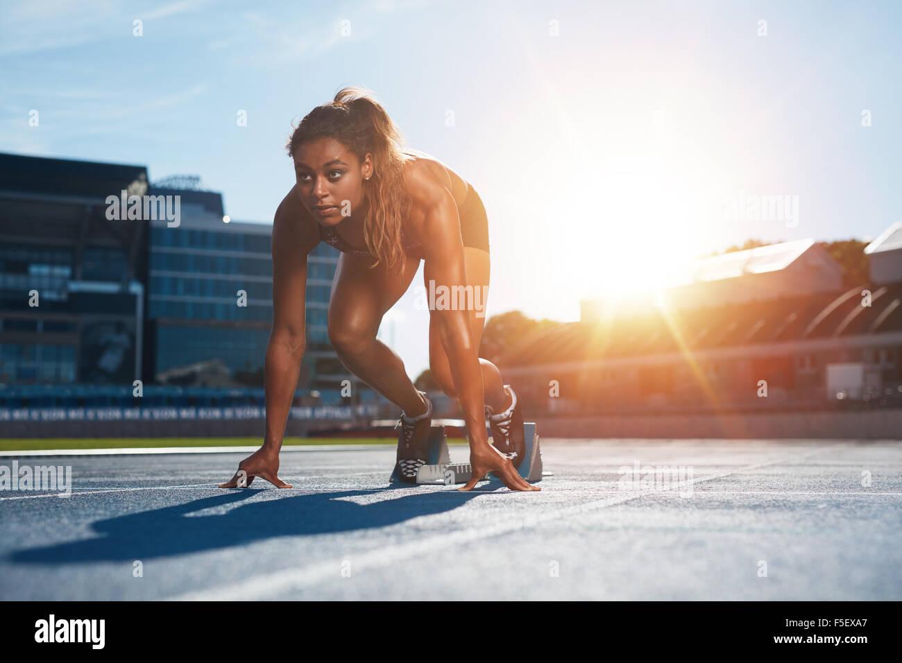 Zuversichtlich Sportlerin in Startposition für den Betrieb bereit. Junge Frau kurz vor dem start eines Sprints Stockbild