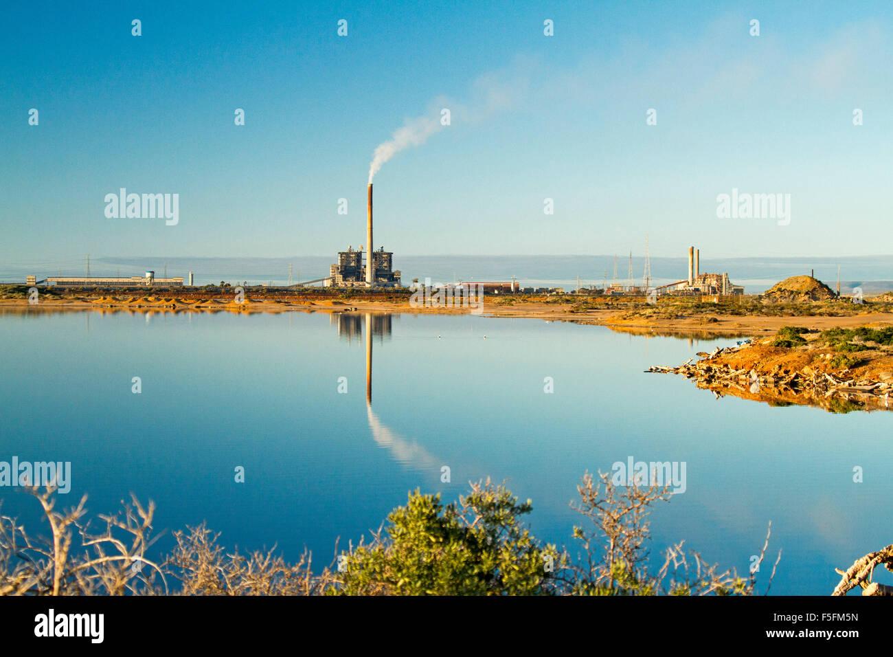 Kohle-Kraftwerk mit dem Rauchen Schornstein spiegelt sich in der Spiegelfläche des blauen Wasser des Spencer Stockbild