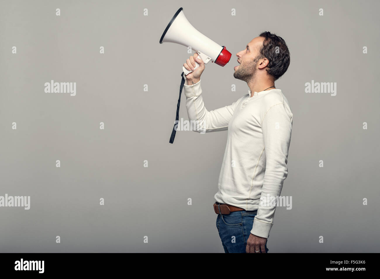 Mann spricht über ein Megaphon, da er eine öffentliche Adresse macht, beteiligt sich an einem Protest Stockbild