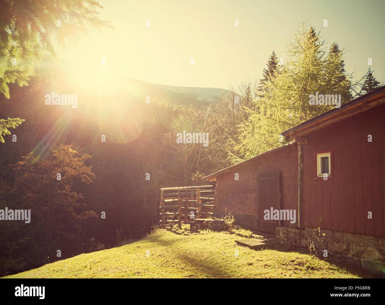 Retro Vintage stilisierte Berghütte gegen Sonne mit Flare-Effekt. Stockbild