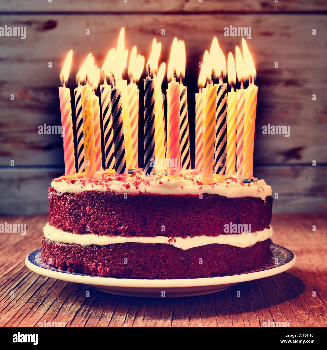 ein Kuchen, garniert mit einigen brennenden Kerzen vor den Kuchen auf einem rustikalen Holztisch mit einem gefilterten Stockbild