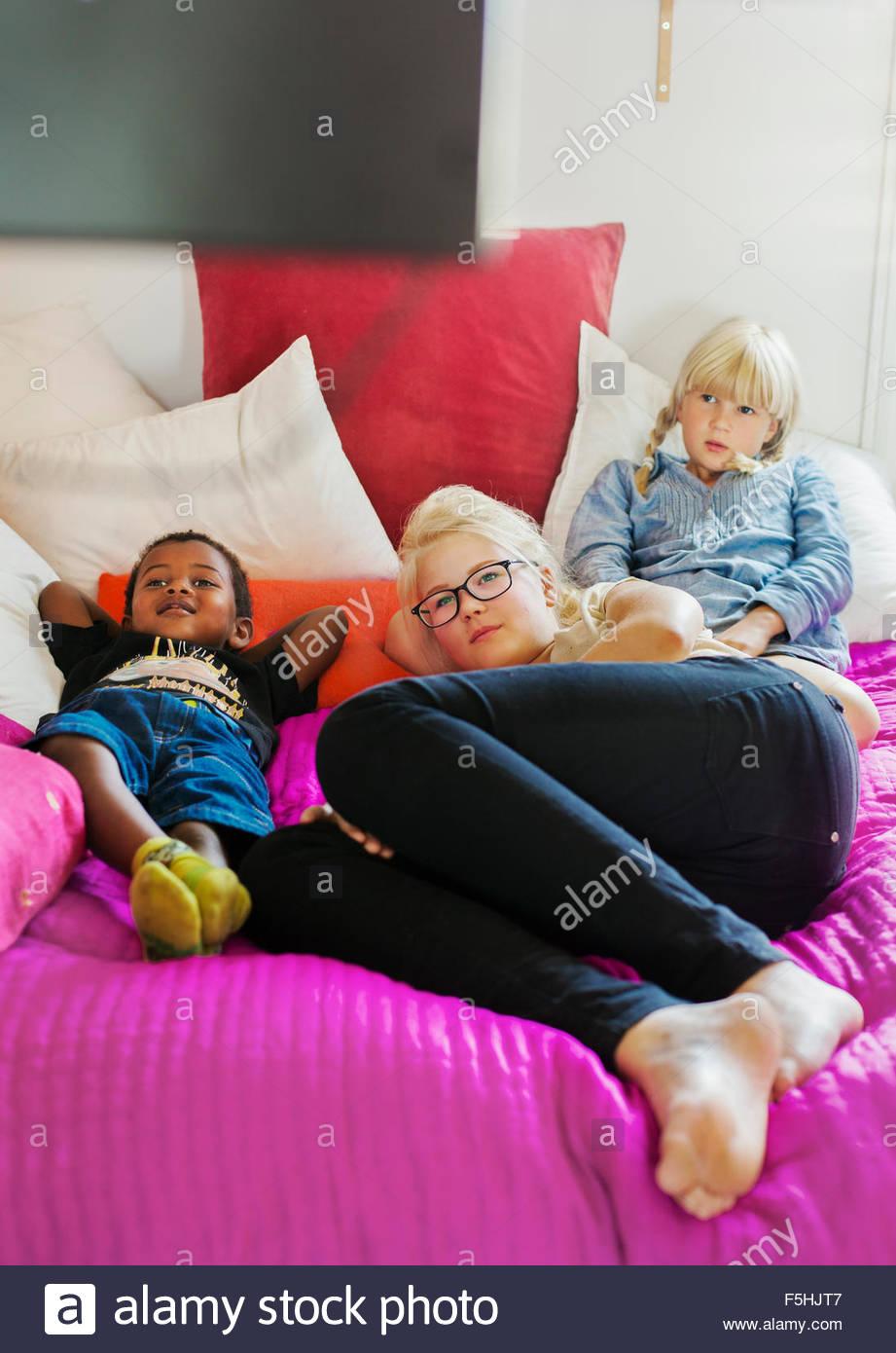 Dänemark, Geschwister (4-5, 10-11, 14-15) vor dem Fernseher zu Hause Stockbild