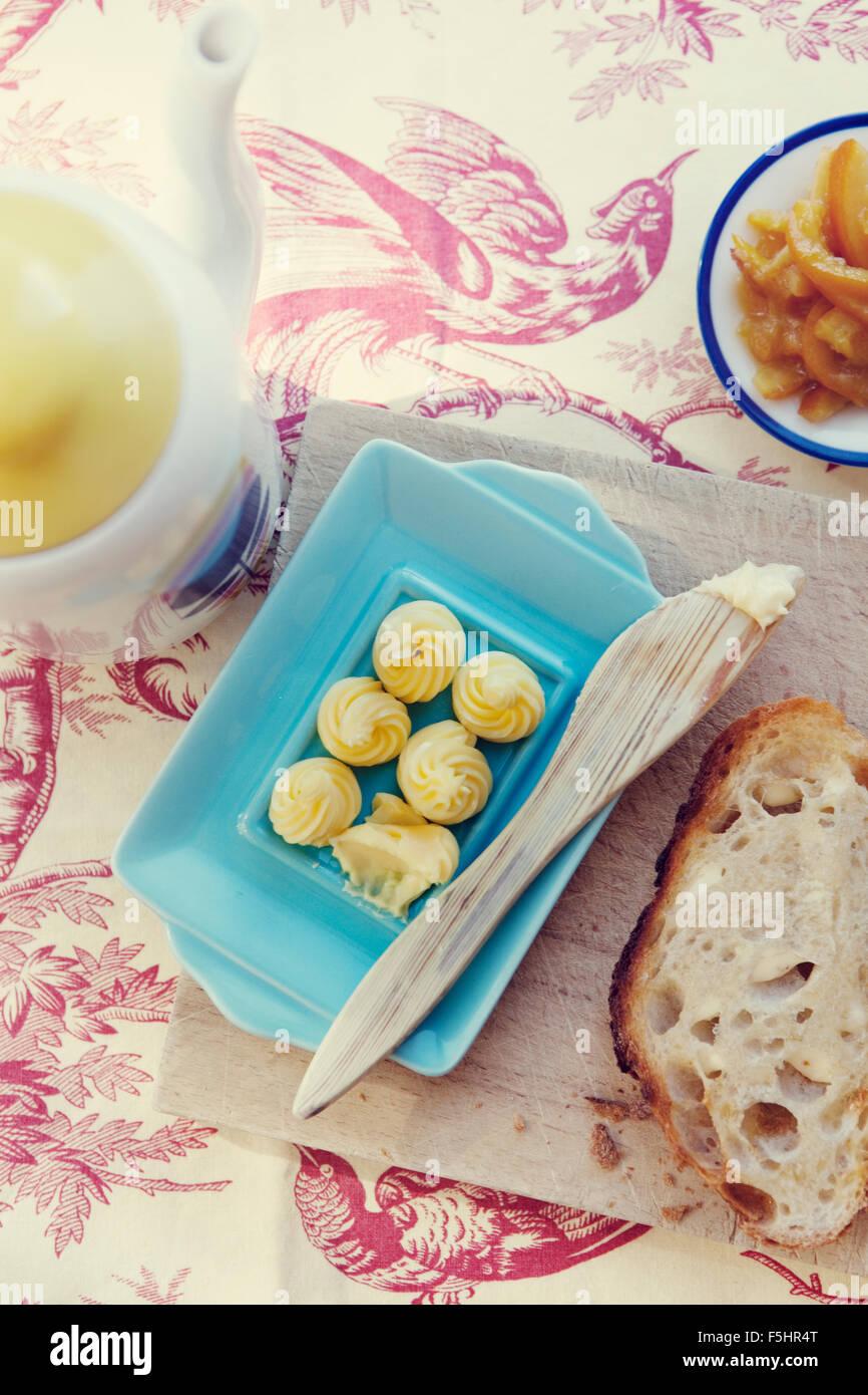 Nahaufnahme von Butter und Brot auf Tischdecke Stockbild