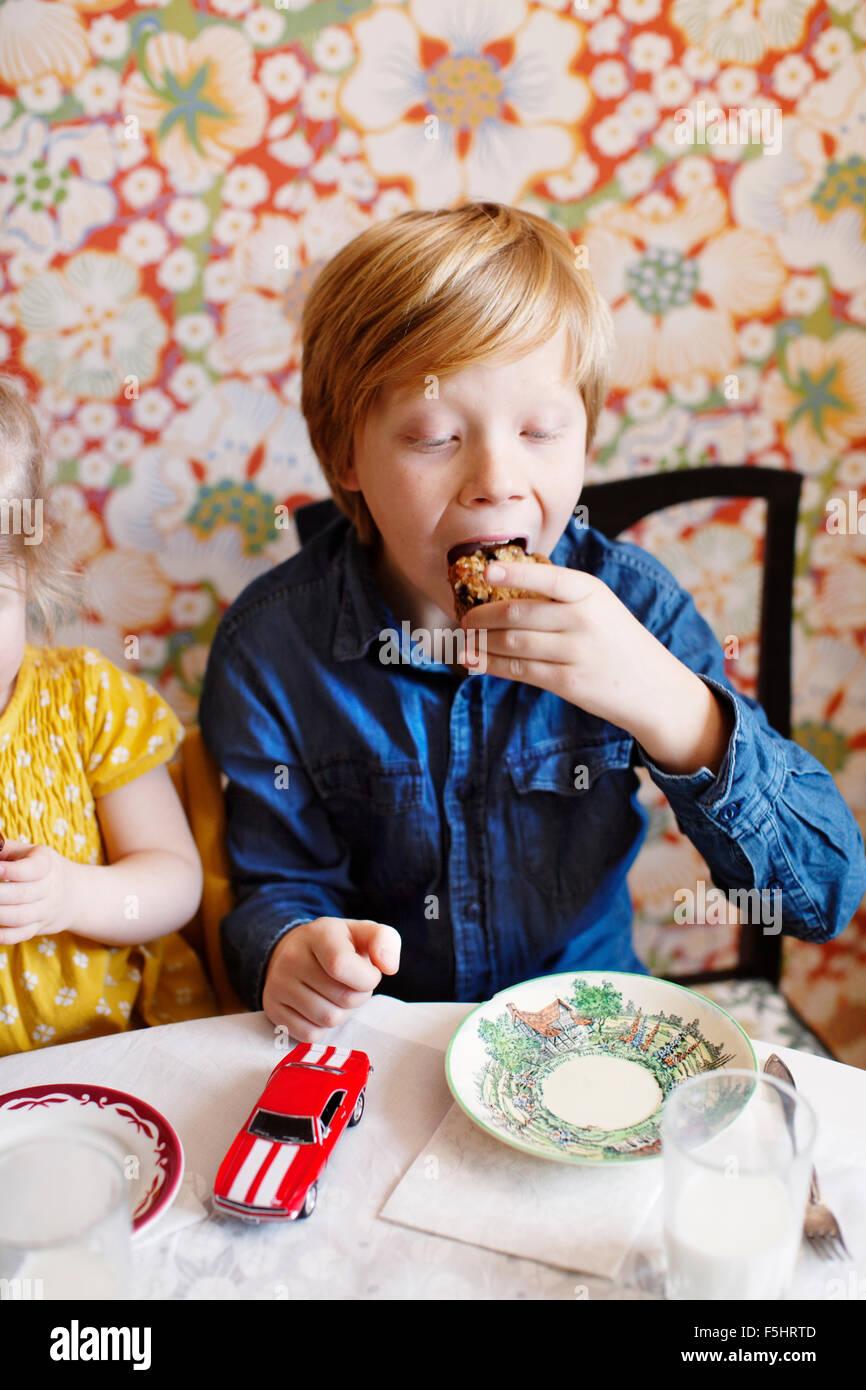 Schweden, junge (10-11) und Mädchen (2-3) essen Kuchen Stockfoto