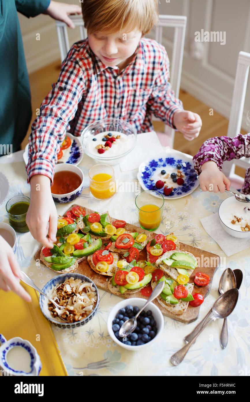 Schweden, Mutter mit zwei Kindern (2-3, 10-11) beim Frühstück Stockbild