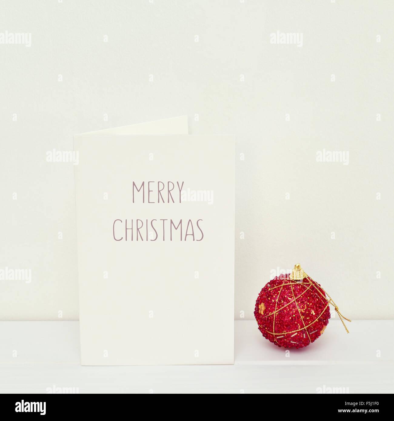 eine rote Weihnachtskugel und eine weiße Grußkarte mit dem Text Frohe Weihnachten in einer weißen Stockbild
