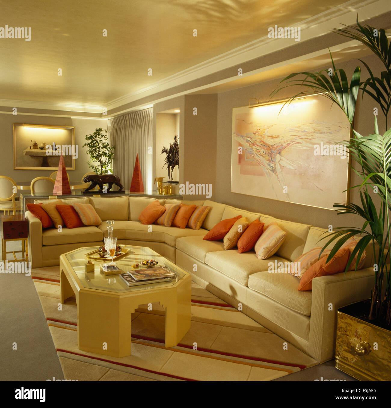 Creme Kaffee Tisch vor einer L-förmigen Creme Sofa mit Kissen in einem 80er Jahre Muskelaufbau Wohnung Wohnzimmer Stockbild