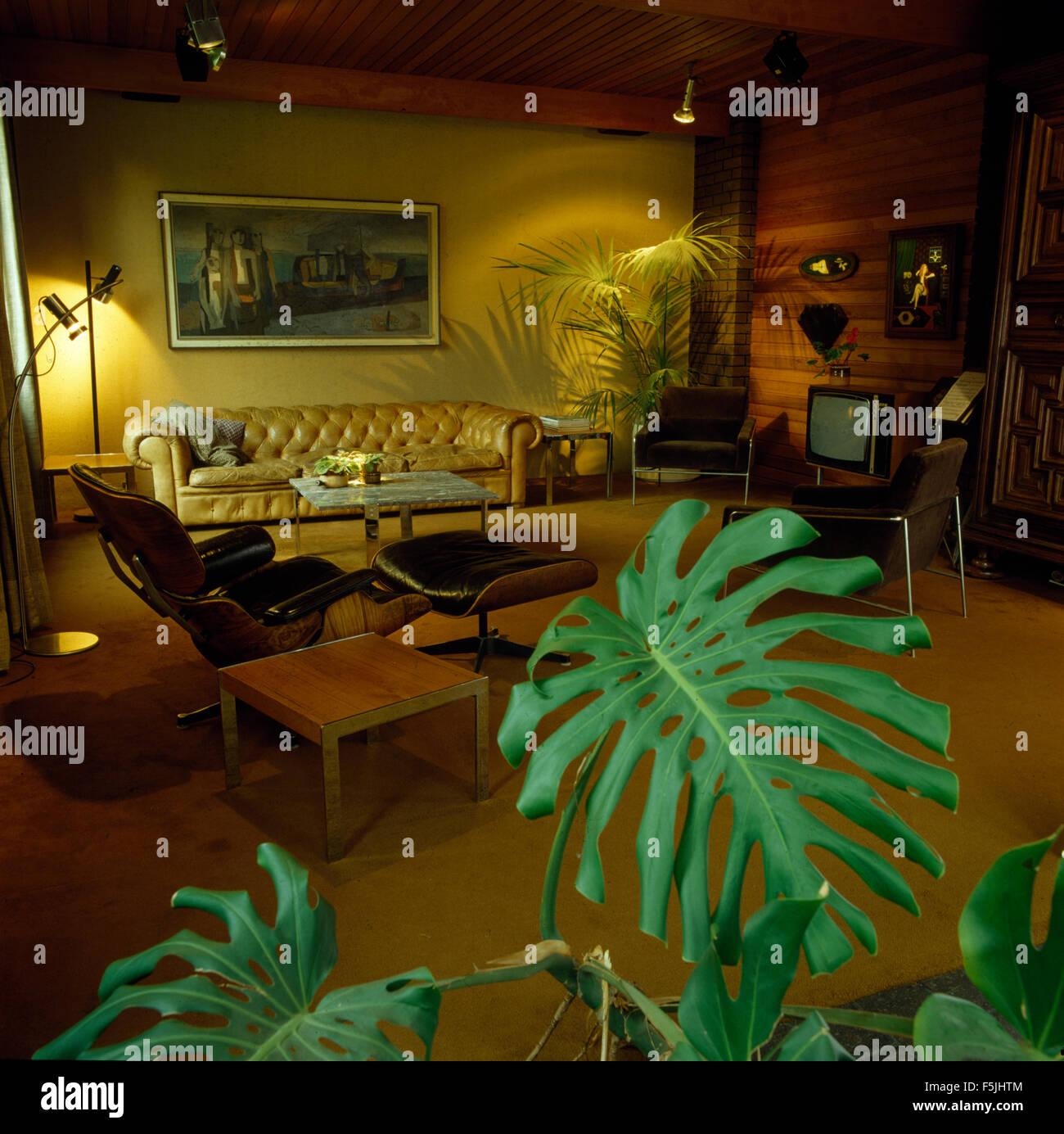 Charles Eames Lounge Chair Und Hocker In Ein Wohnzimmer Mit Einem Leder  Chesterfield Sofa Und Grüne Zimmerpflanzen Siebziger