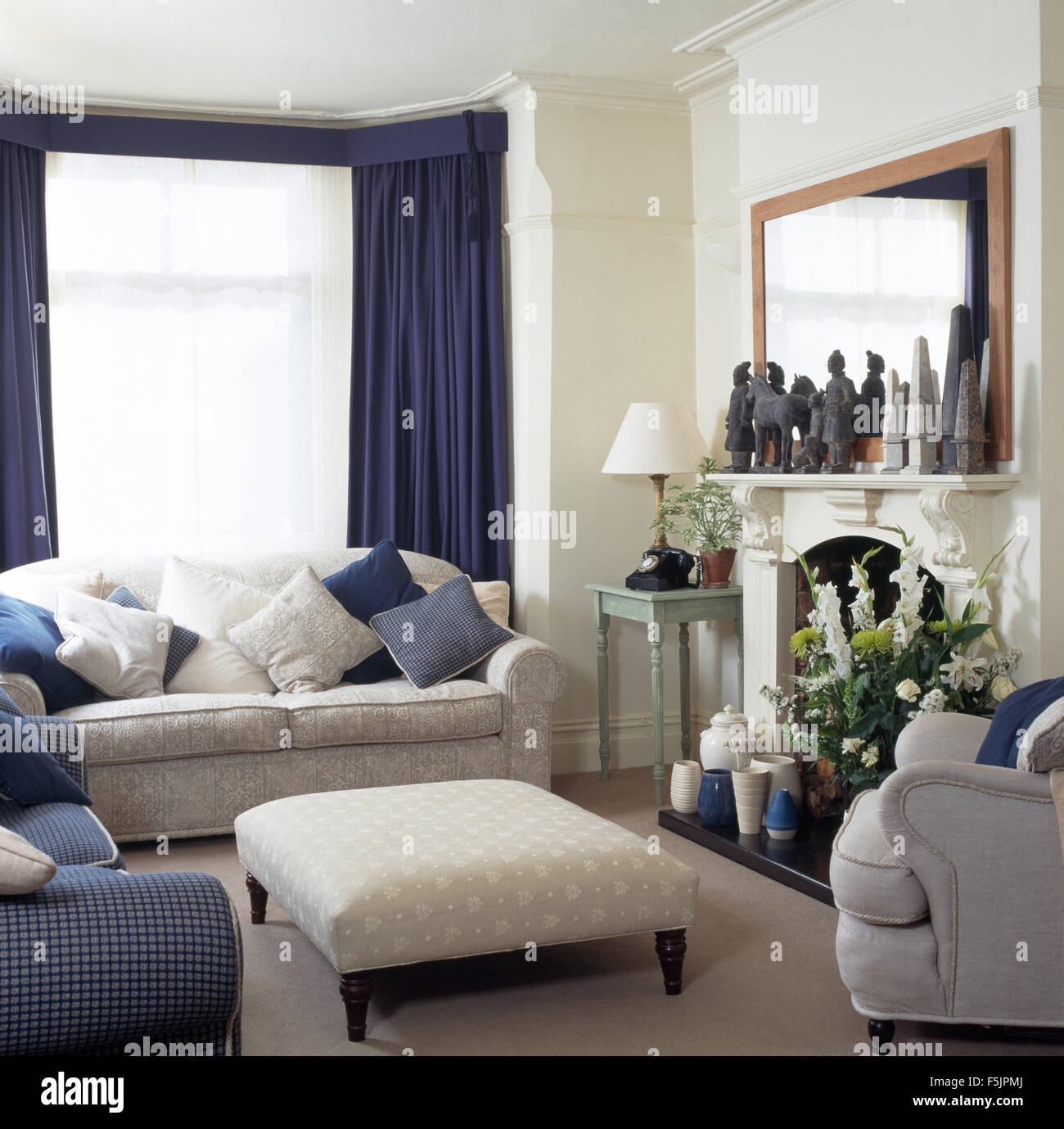 Sahne Sofa Und Ottoman Hocker In Einem Reihenhaus Wohnzimmer Mit Blauen  Vorhängen Im Fenster