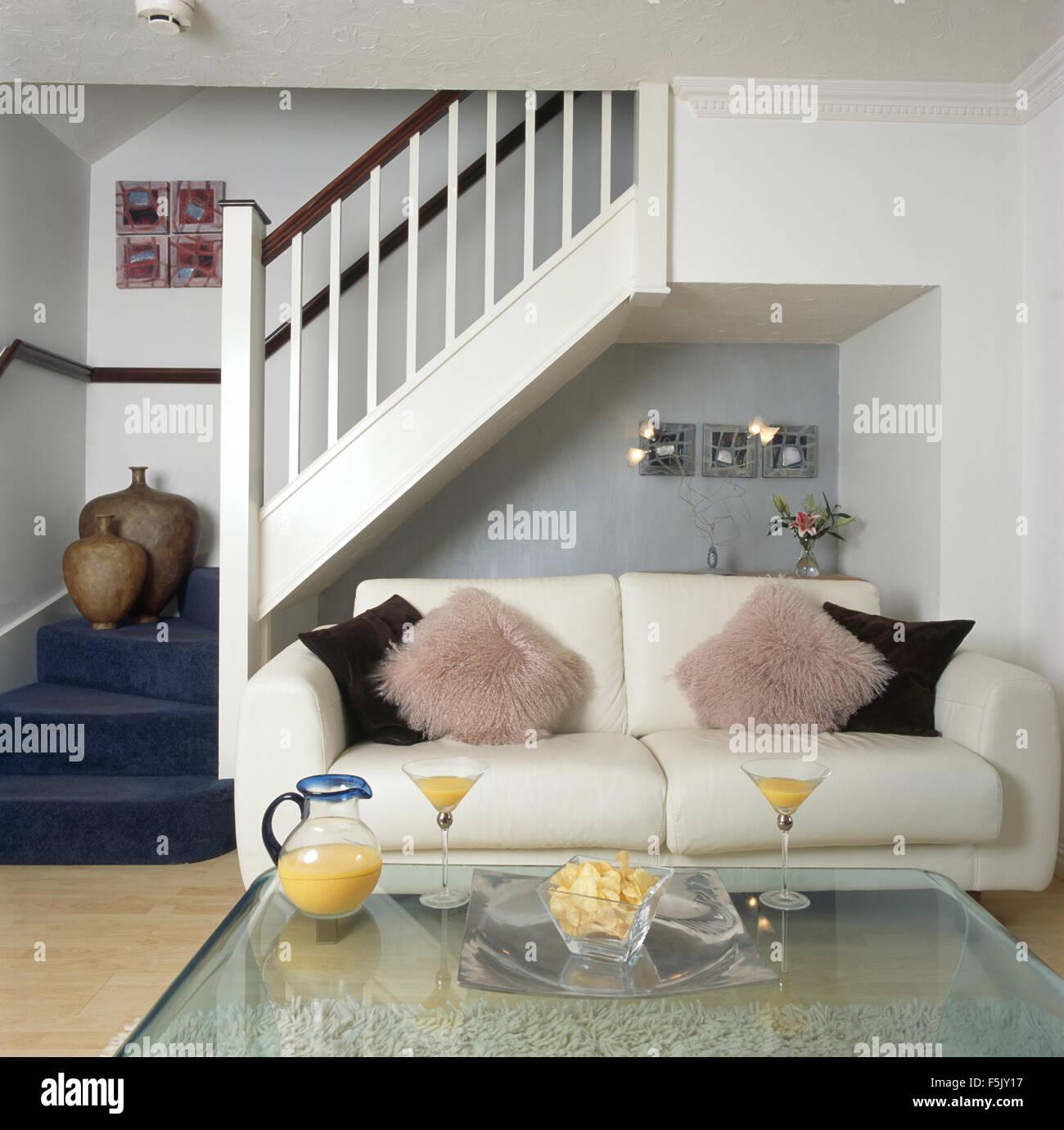 Flauschige Kissen auf weißen Sofa neben Treppe im Wohnzimmer im Stil ...