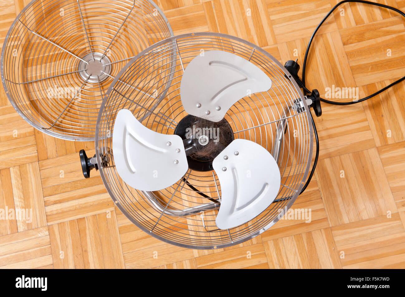 Verworrenen menschliches Haar in ein Fan, Haushalt elektrische Boden Chrom Ventilator Maschine mit dem Drehen der Stockbild
