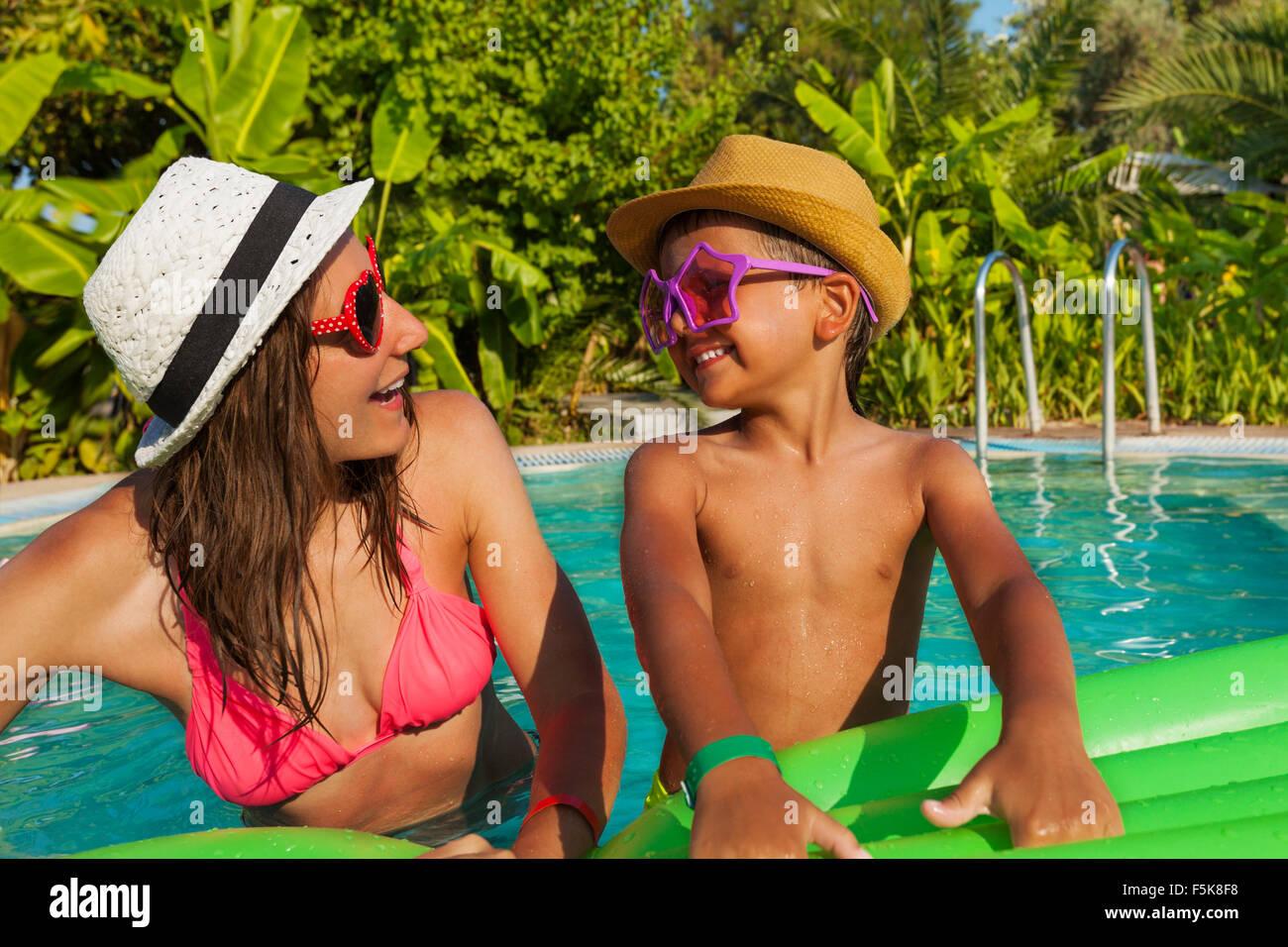 Glückliche Mama und ihr Sohn das Tragen von Sonnenbrillen im pool Stockfoto