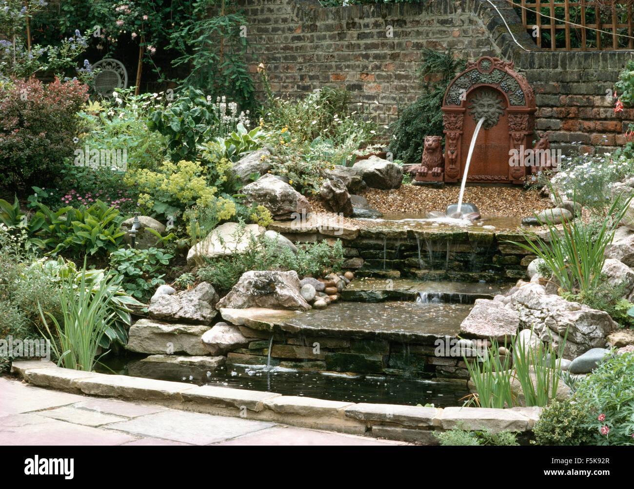 Löwenbrunnen an Wand über dem Wasserfall über Steinstufen gesäumt ...