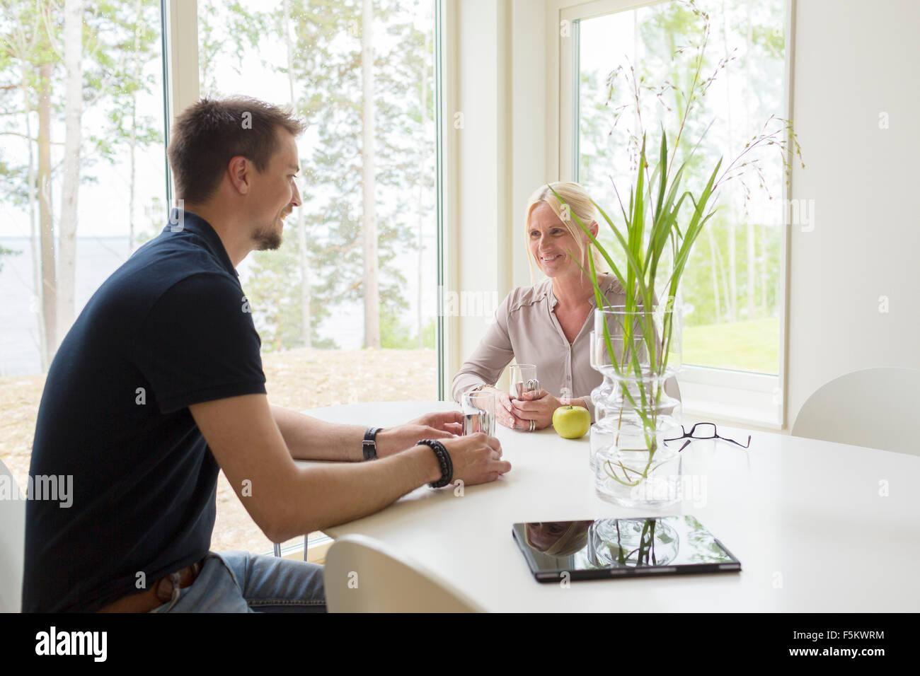 Schweden, Mann und Frau sitzen und trinken zu Hause Stockbild