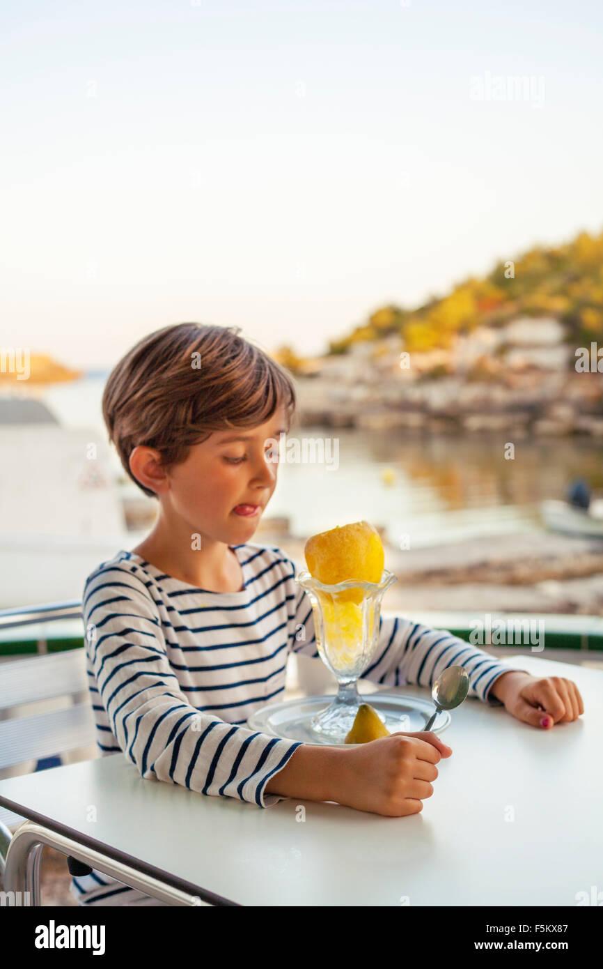 Spanien, Menorca, Boy (6-7) lecken Lippen beim betrachten orange Stockbild