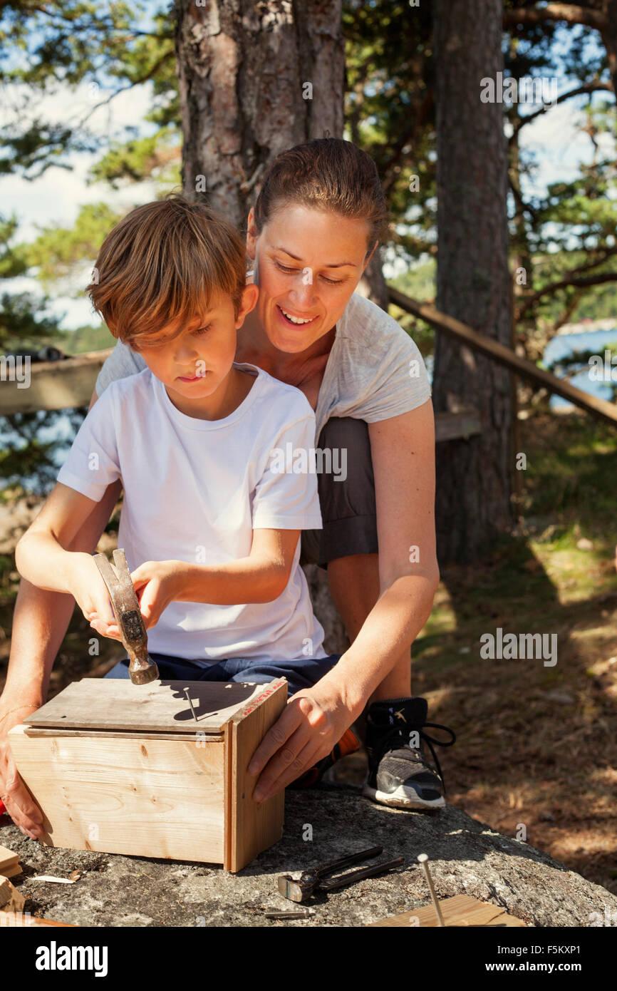 Schweden, Uppland, Runmaro, Barrskar, Mutter hilft Sohn (6-7), Vogelhaus zu bauen Stockbild