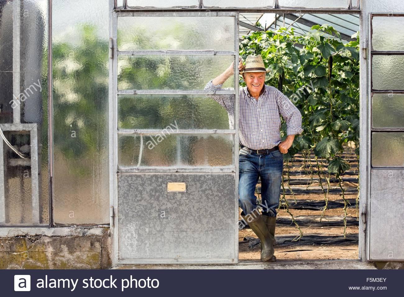 Ältere Mann mit Hut und Gummistiefel gelehnt Treibhaus Tür Blick auf die Kamera zu Lächeln Stockbild