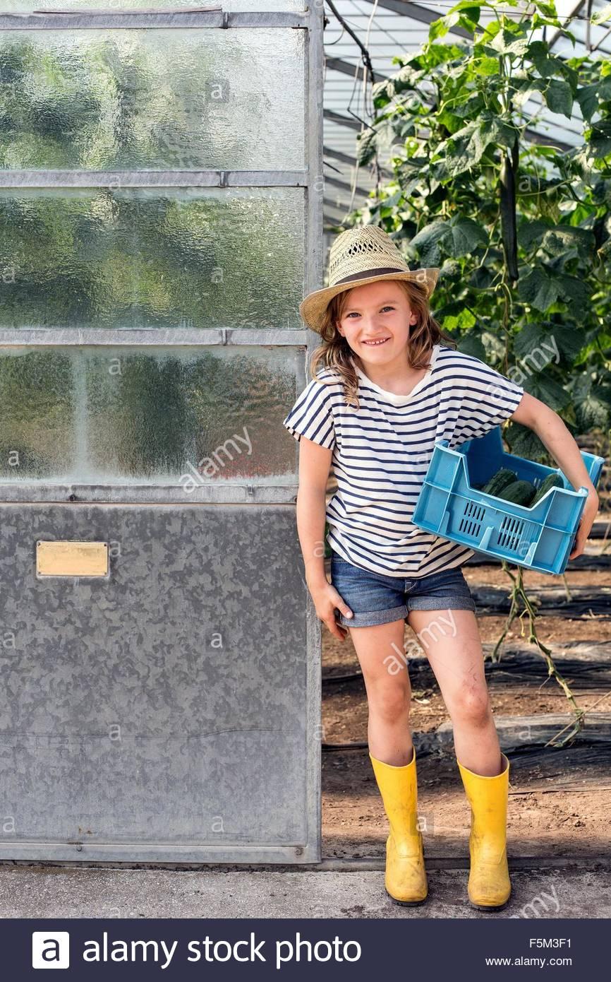 Mädchen tragen Gummistiefel und Hut stehen im Treibhaus Tür hält Tablett Blick auf die Kamera zu Stockbild