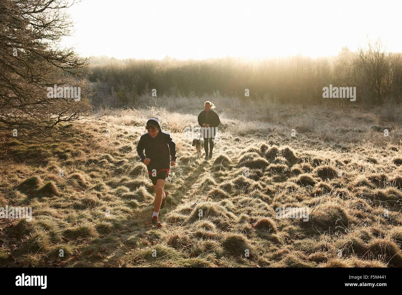 Hohen Winkel Vorderansicht des Mutter, Sohn und Hund läuft auf der Weide Stockbild
