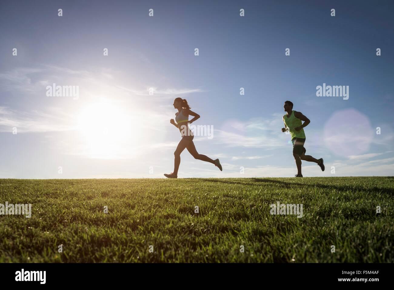 Sonnendurchflutetes Mann und Frau im Park laufen Stockbild