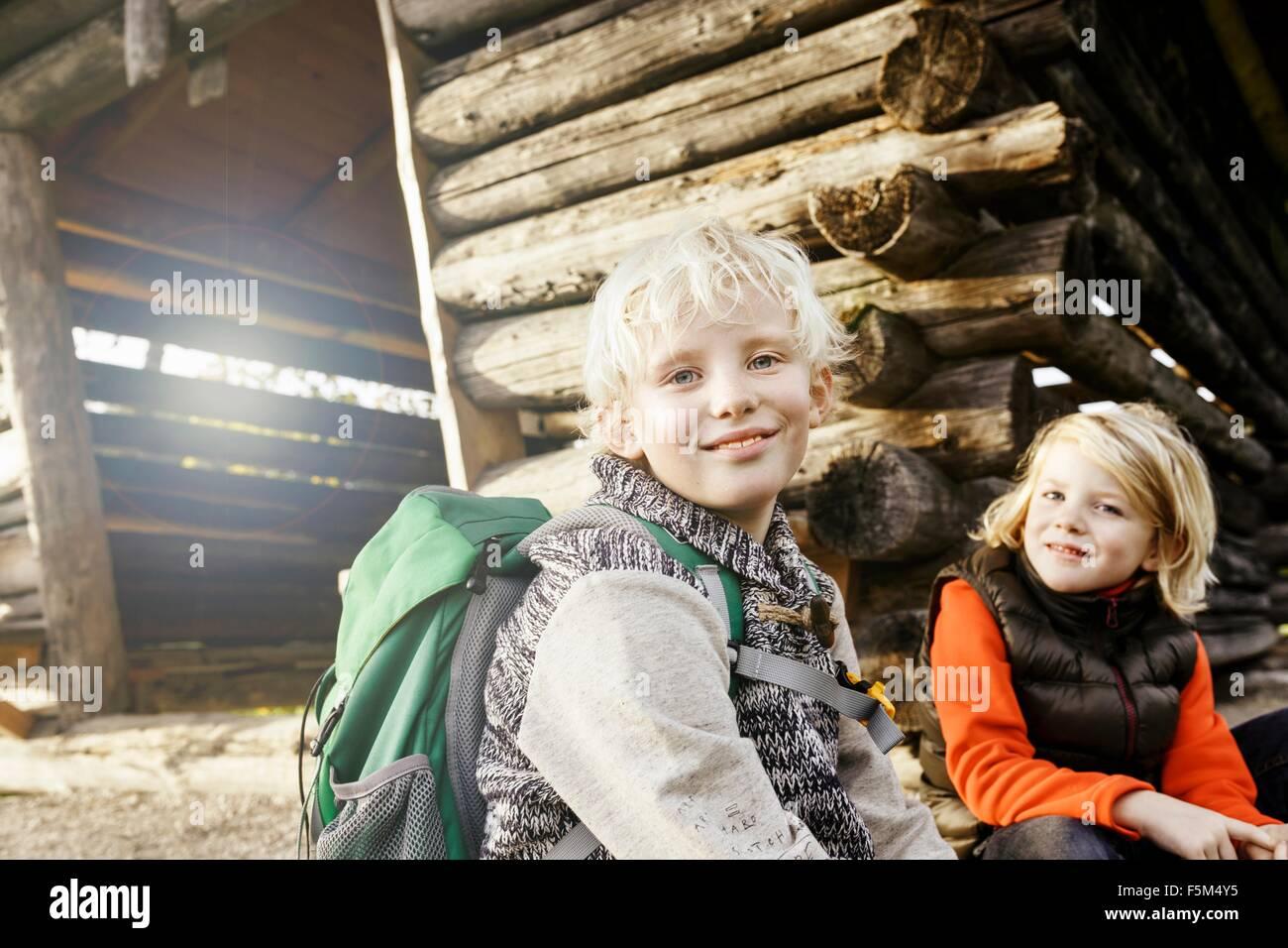 Blonde kurzhaarige Bruder und Schwester sitzen außerhalb Blockhaus mit Blick auf die Kamera zu Lächeln Stockbild