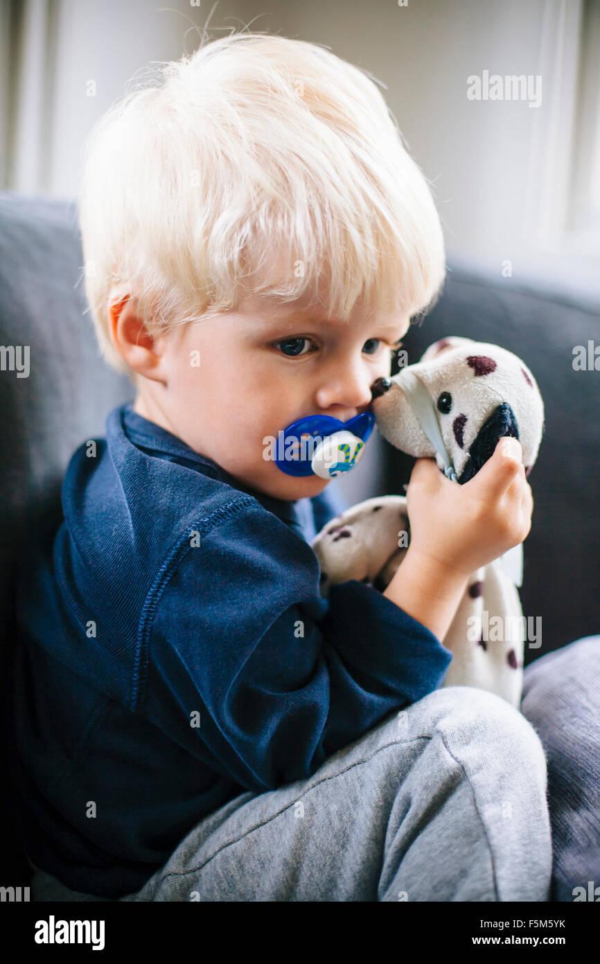 Schweden, Boy (4-5) mit Schnuller und Spielzeug Stockbild
