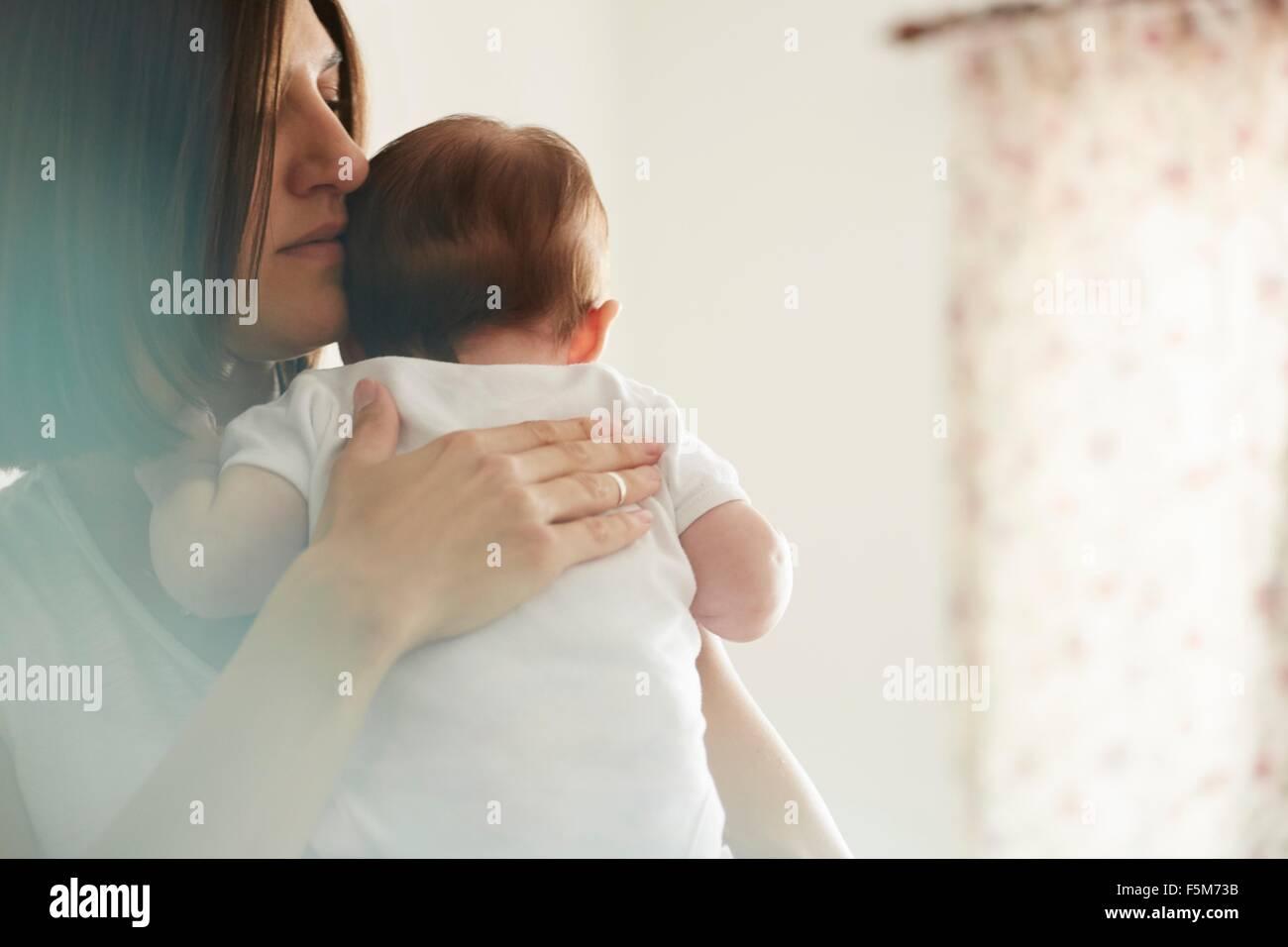 Mutter mit Baby im Schlafzimmer Stockbild