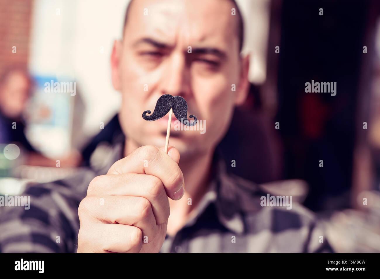 ein junger kaukasischen Mann hält einen falschen Schnurrbart in einem Stick vor seinem Gesicht Stockbild
