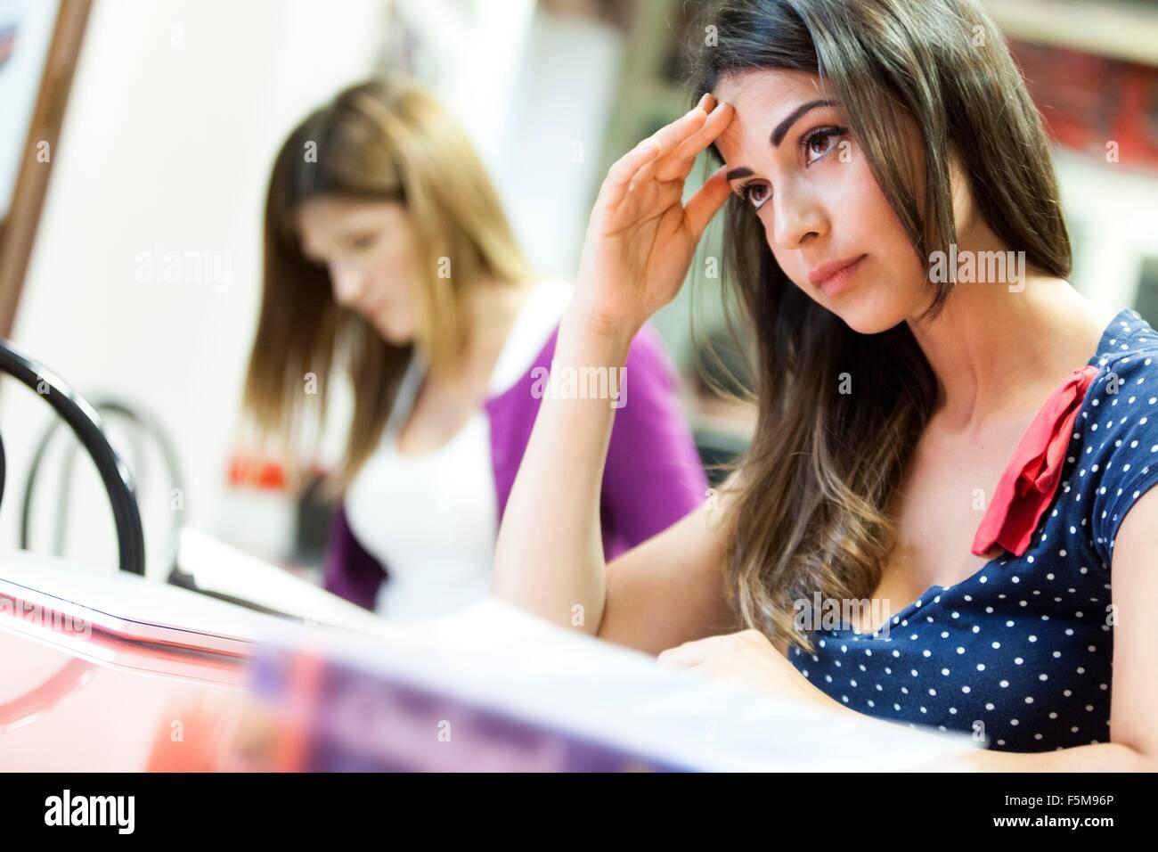 Junge Frau sitzt am Schreibtisch, Studium, nachdenklichen Ausdruck Stockbild