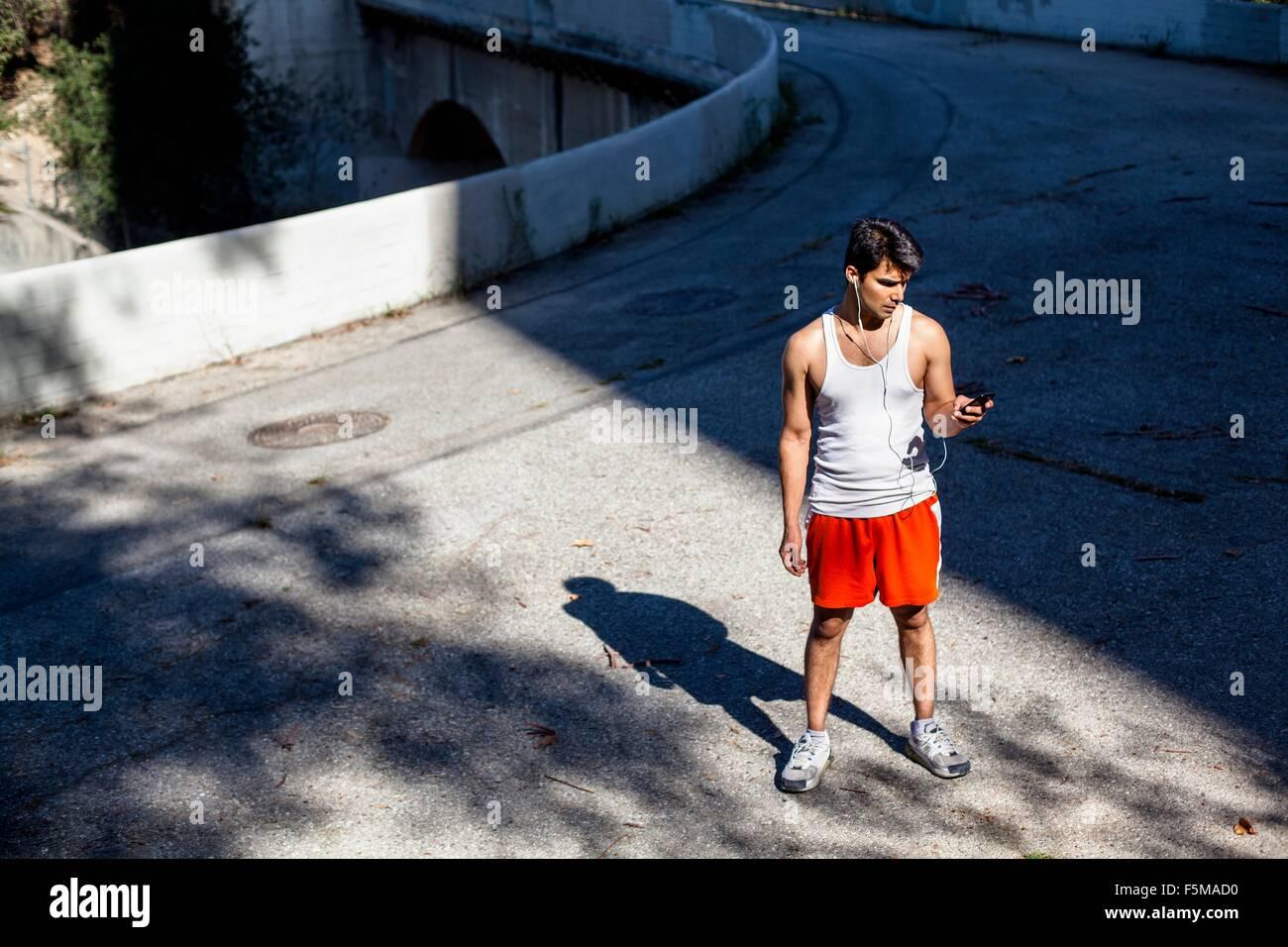 Jogger, die Auswahl der Musik auf Smartphone, Arroyo Seco Park, Pasadena, Kalifornien, USA Stockbild