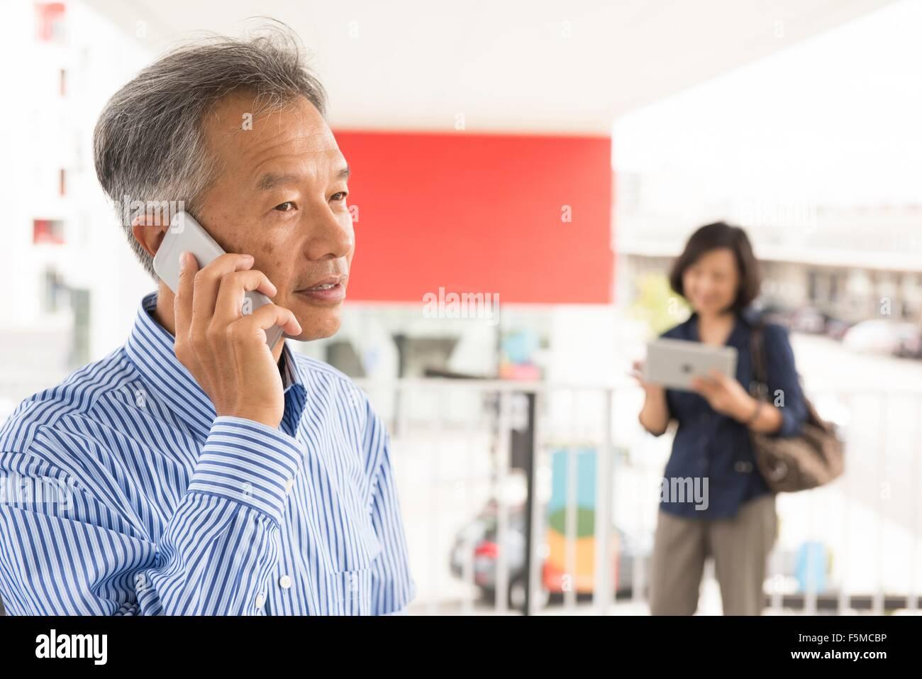 Kopf und Schultern von reifer Mann sprechen auf Smartphone wegschauen Stockbild